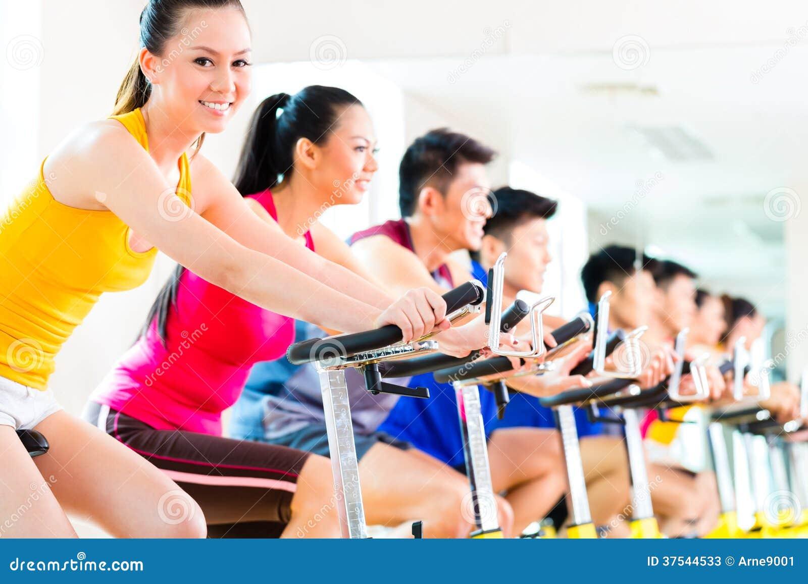 Gente asiática en el entrenamiento de giro de la bici en el gimnasio de la aptitud
