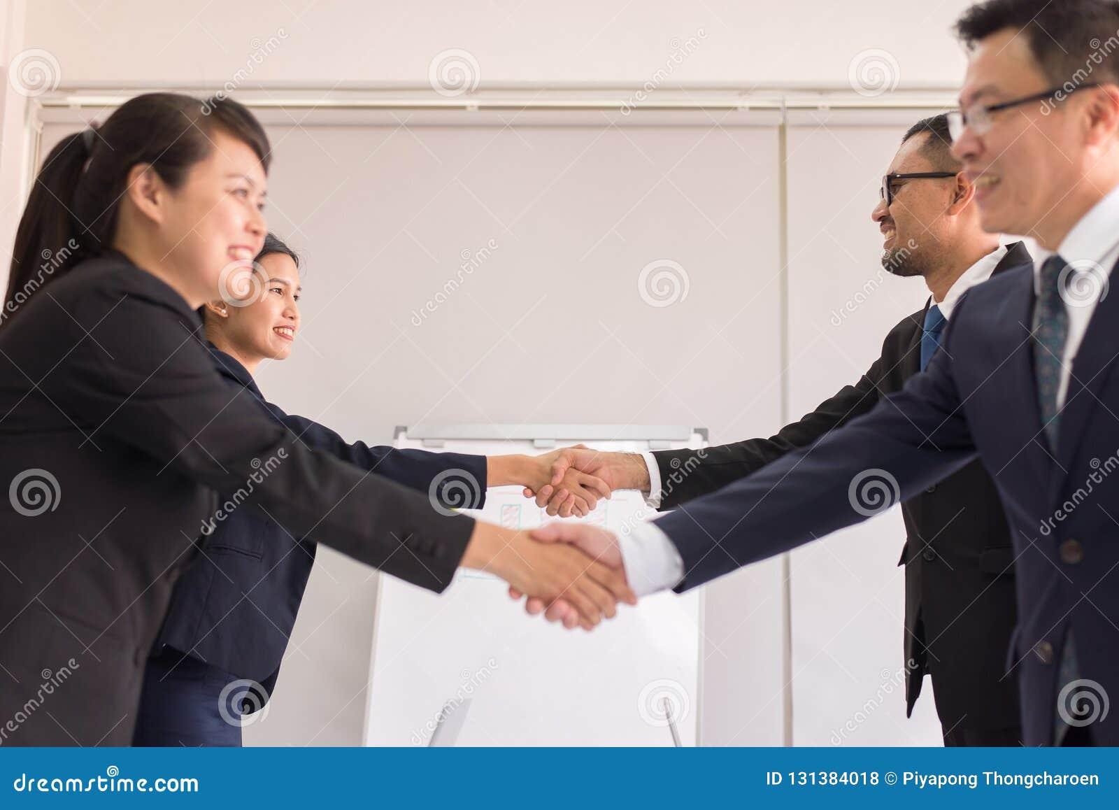Gente asiatica del gruppo di affari in vestito convenzionale che stringe le mani che finiscono su riunione, fuoco selettivo, asso