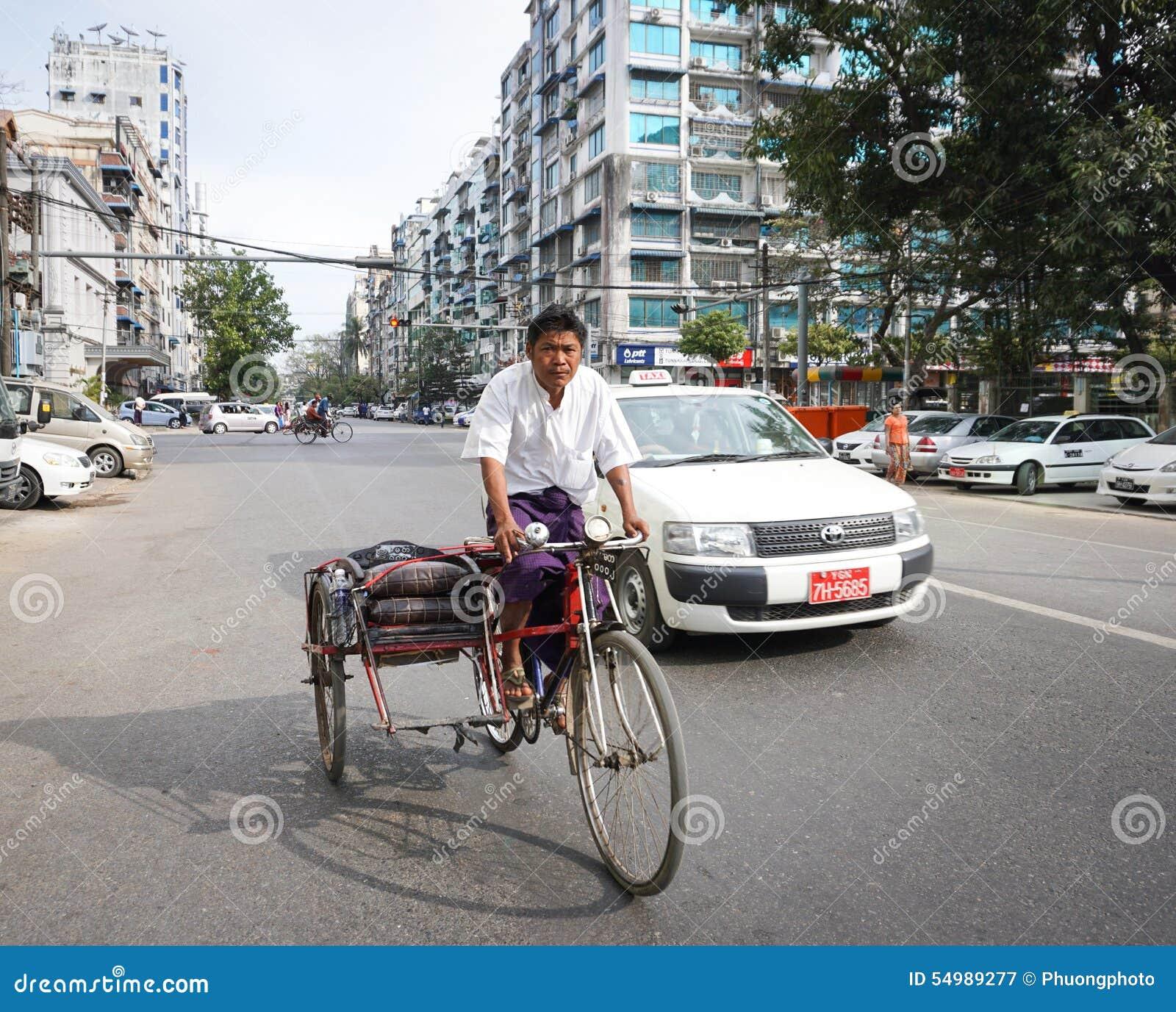 Gente, coches y bicis en las calles en Mandalay