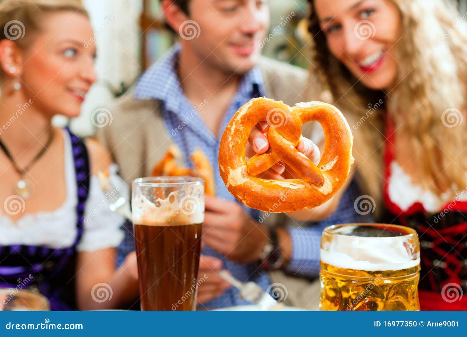 Gente con la cerveza y el pretzel en pub bávaro