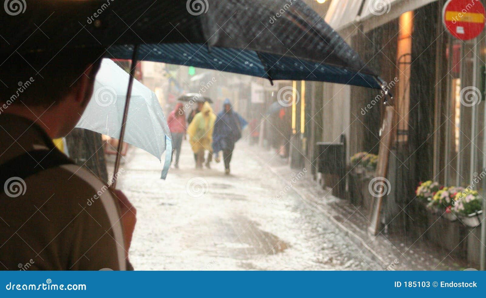 Gente con los paraguas en la lluvia