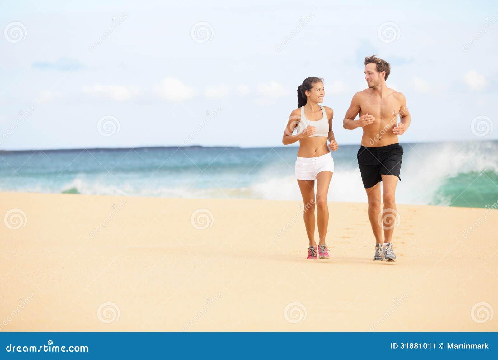 Gente corriente - pares de los corredores en funcionamiento de la playa