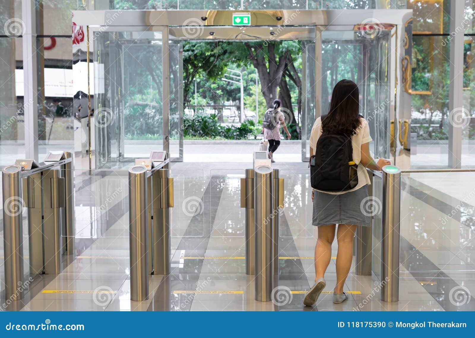 Gente de las mujeres que sale de seguridad en una puerta de la entrada con el edificio de oficinas elegante del control de acceso