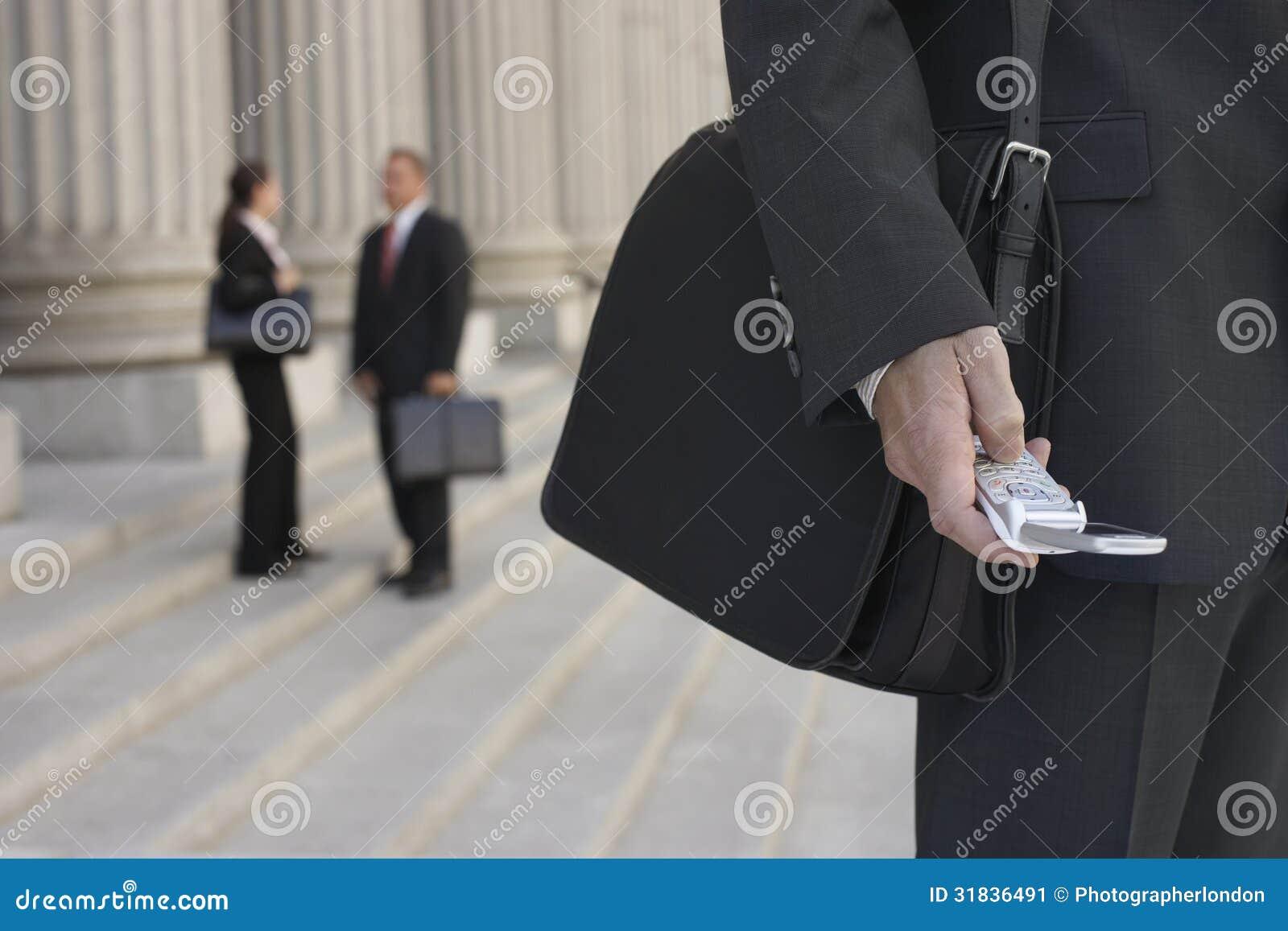 Gente de Using Cellphone And del hombre de negocios que habla en fondo
