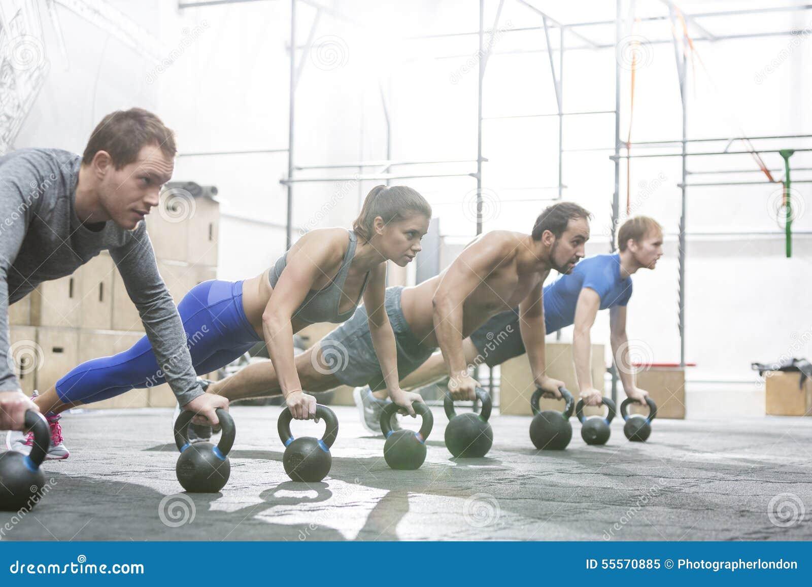Gente dedicada que hace flexiones de brazos con los kettlebells en el gimnasio del crossfit