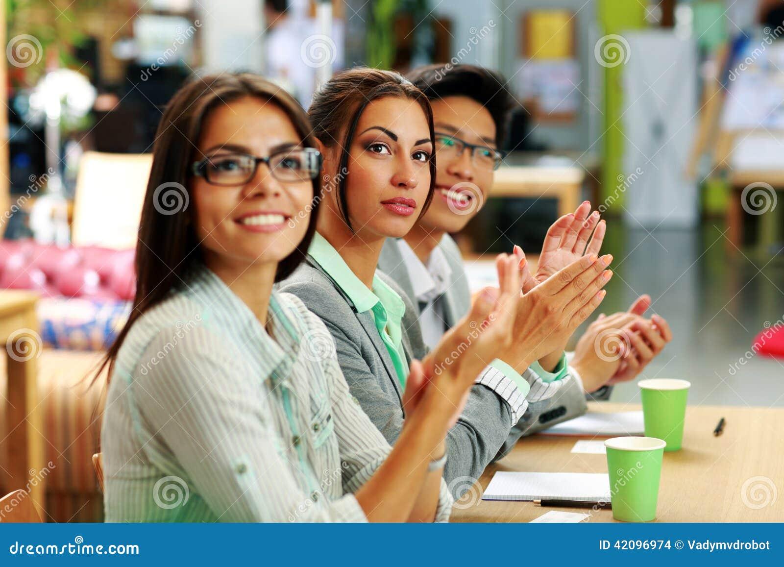Gente di affari che applaude in una riunione