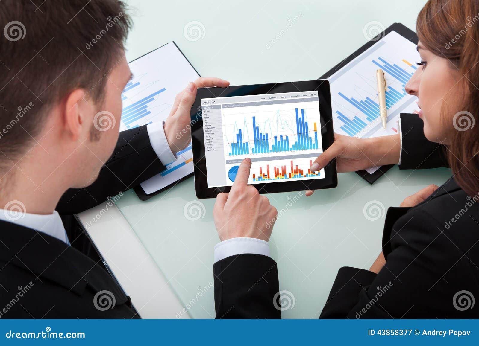 Gente di affari che discute sopra i grafici sulla compressa digitale