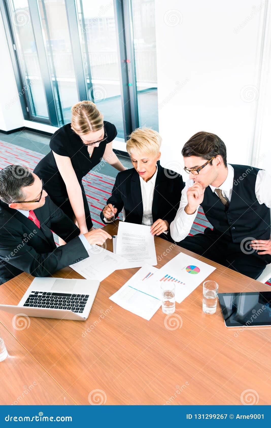 Gente di affari che esamina lavoro di ufficio di dati finanziari