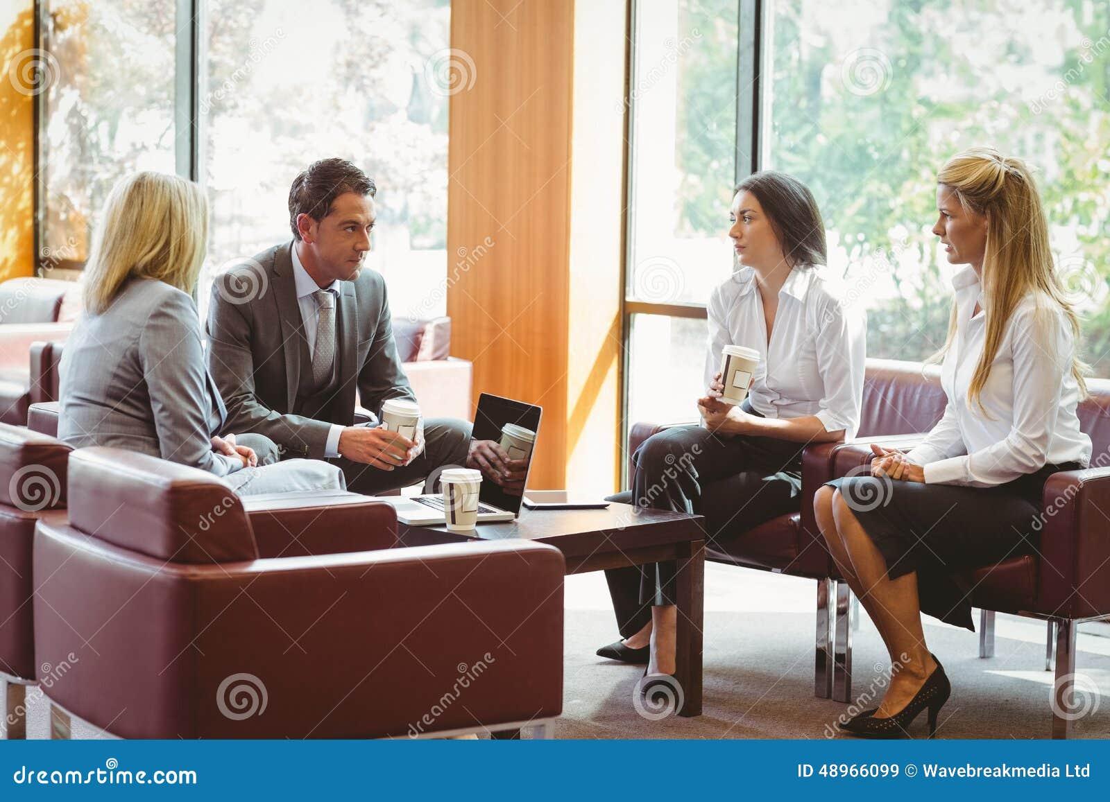 Gente di affari che parla insieme e che lavora sul sofà