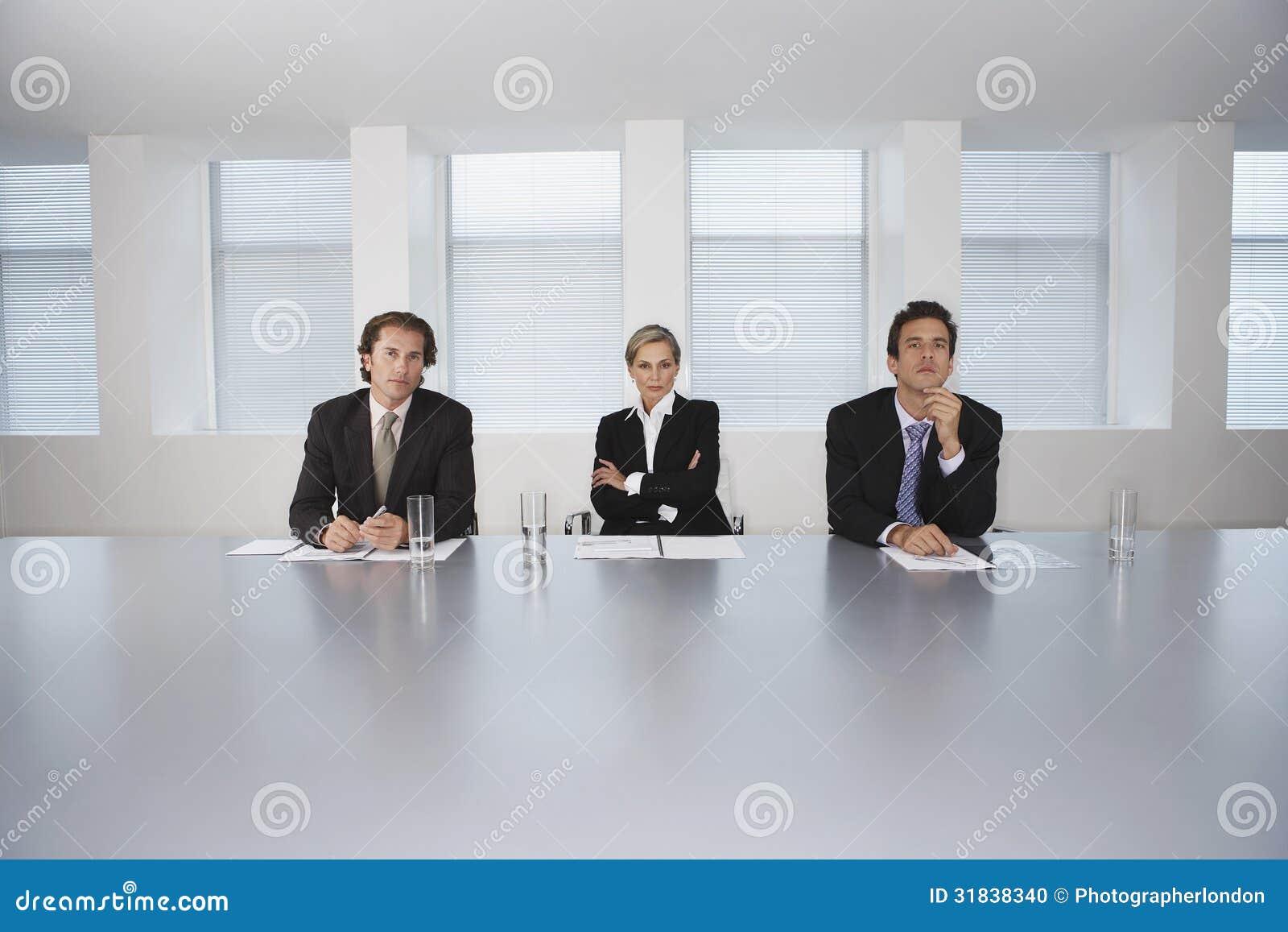 Gente di affari che si siede alla Tabella di conferenza