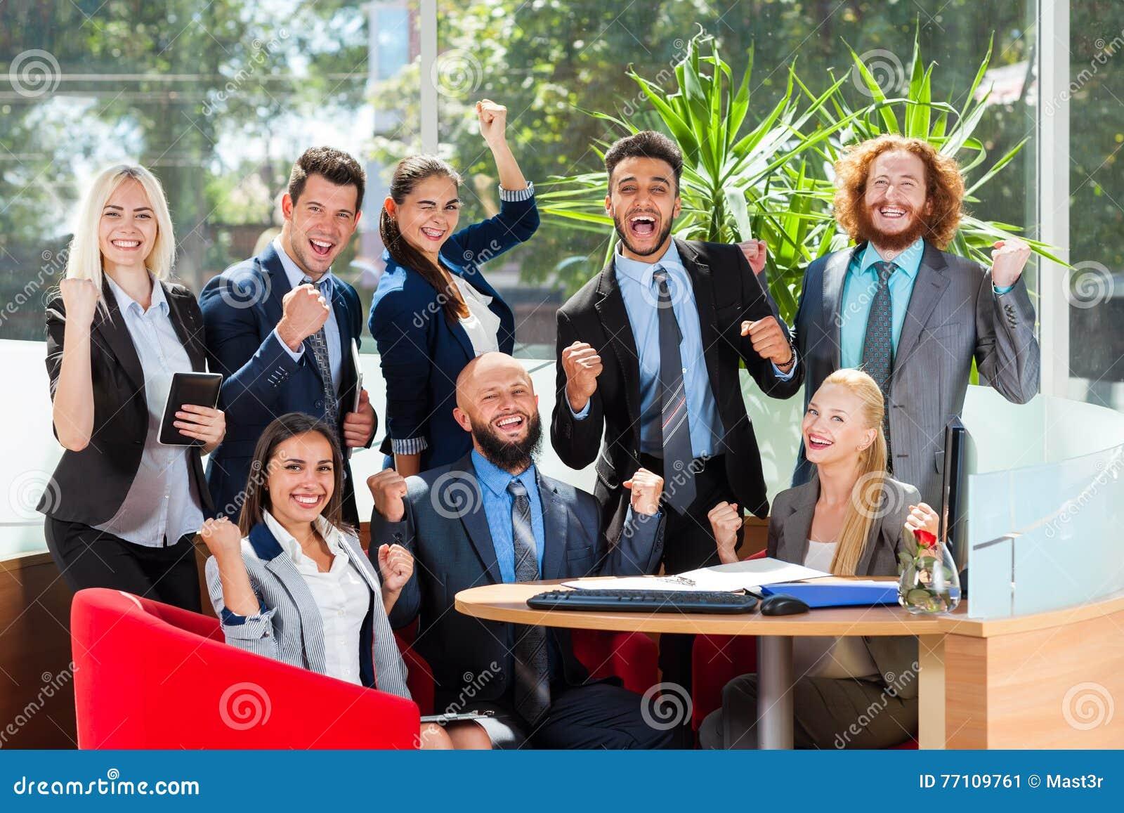 Gente di affari del gruppo Sit At Desk, riuscito Team In Modern Office emozionante, sorriso felice delle persone di affari con al