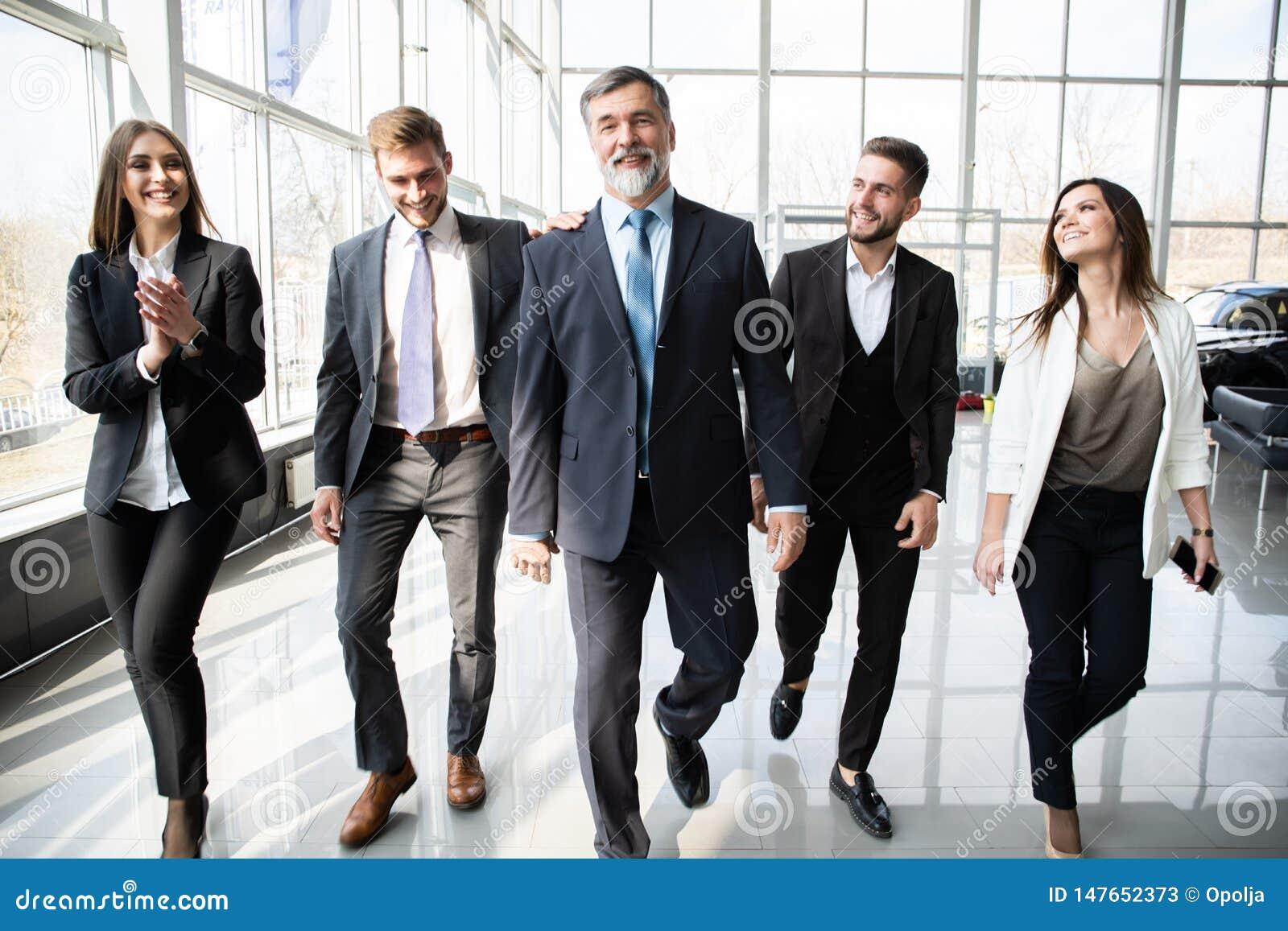 Gente di affari di Team Walking In Modern Office, uomini d affari sicuri e donne di affari con il capo maturo In Foreground