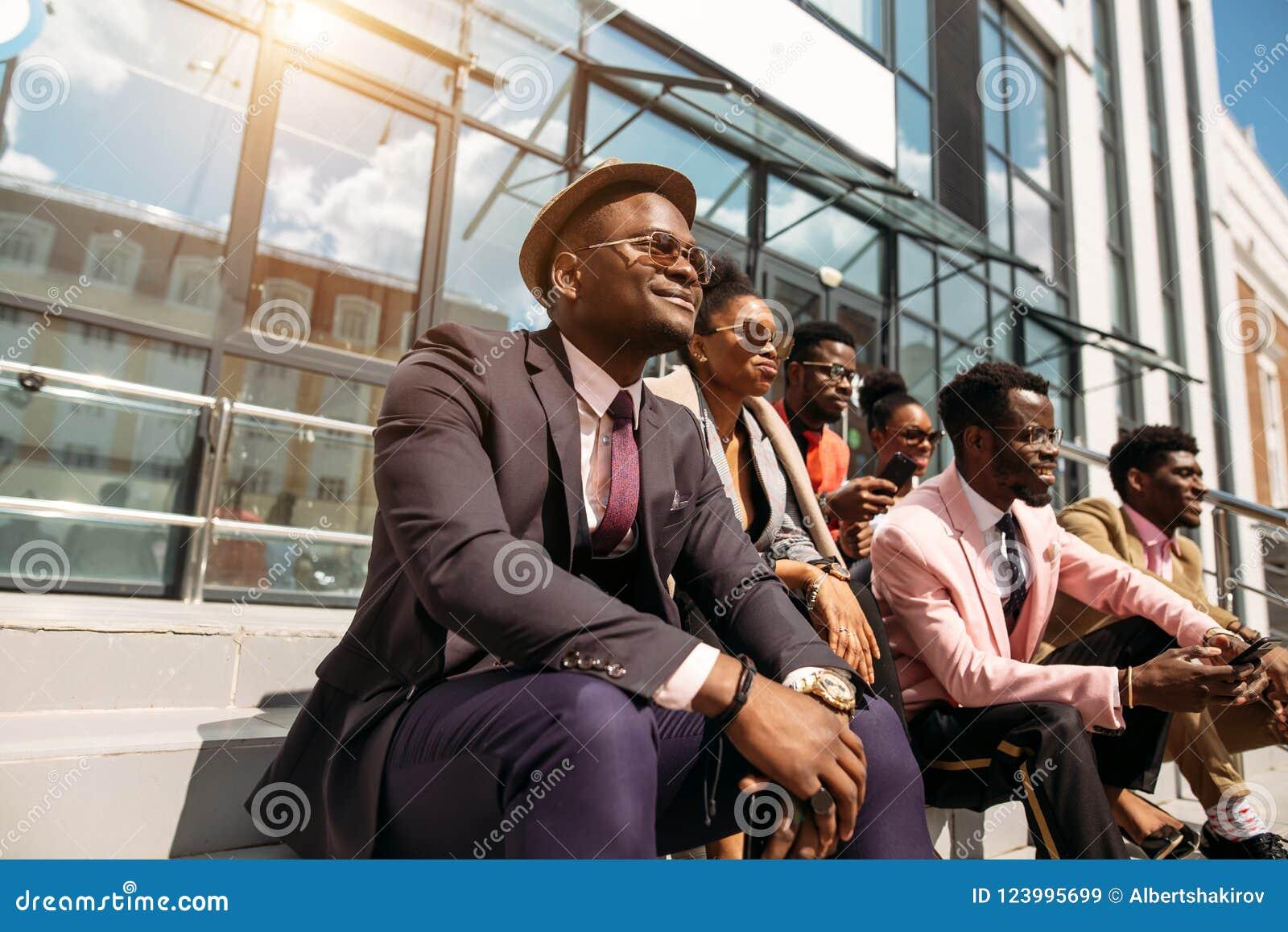 Gente elegante relajada con las caras optimistas