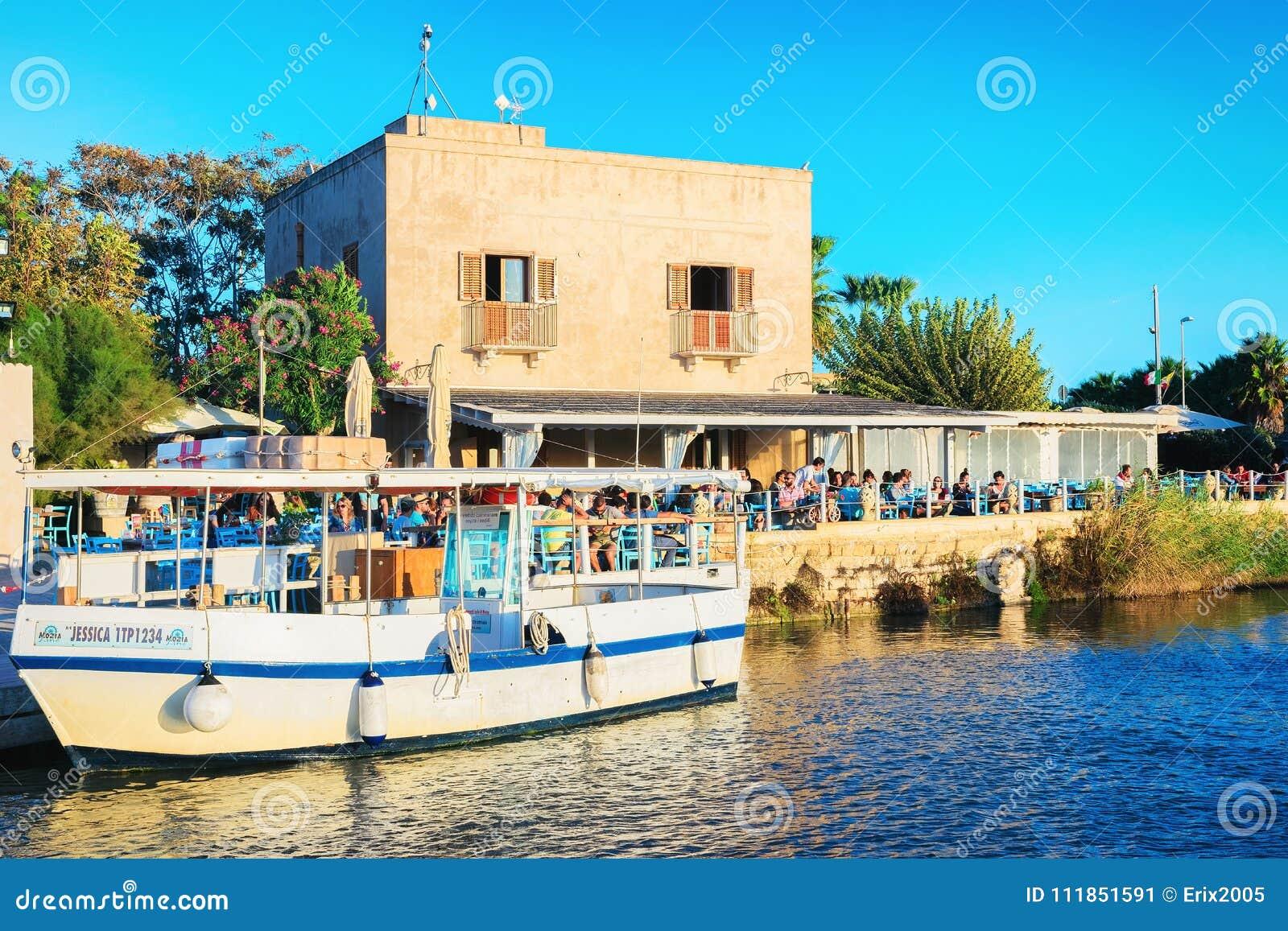 Gente en café de la calle en la marsala Sicilia de la charca de la evaporación de la sal