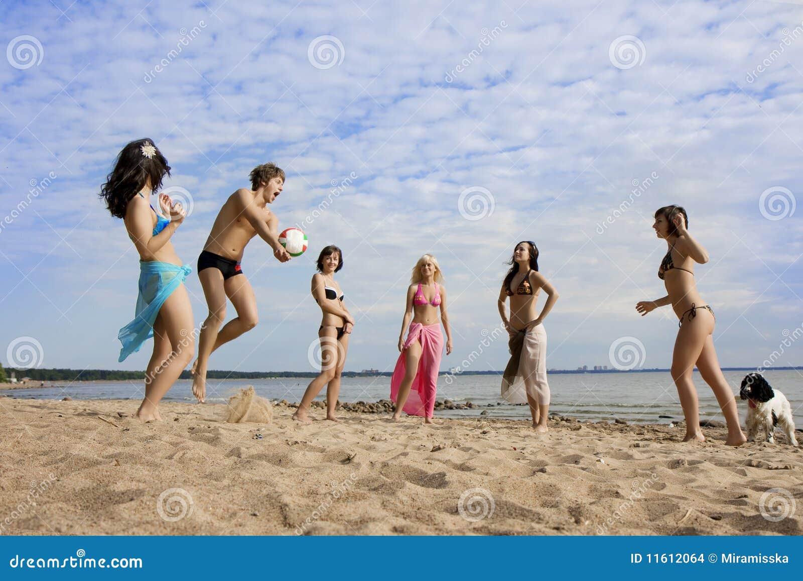 Gente en la playa que juega a voleibol