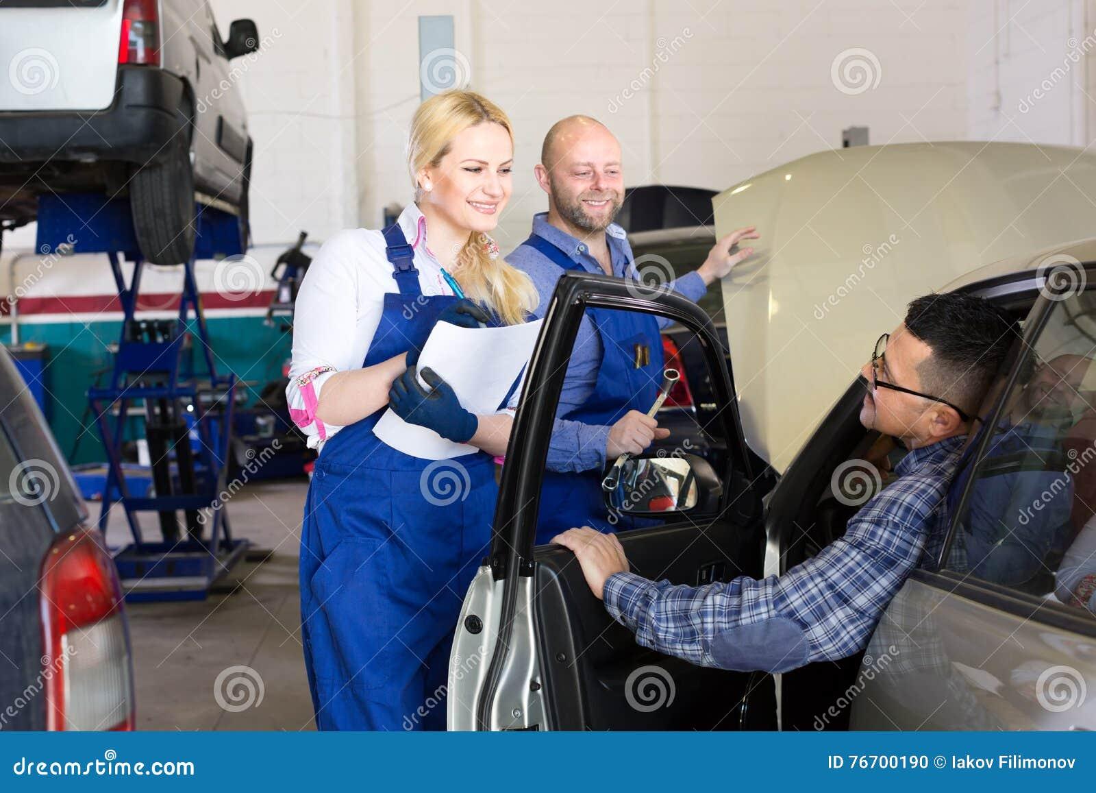 Gente en un taller del servicio del coche