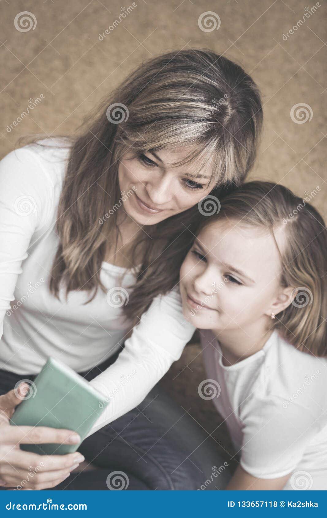 Gente, familia y concepto de la tecnología - muchacha y madre felices con smartphone en casa