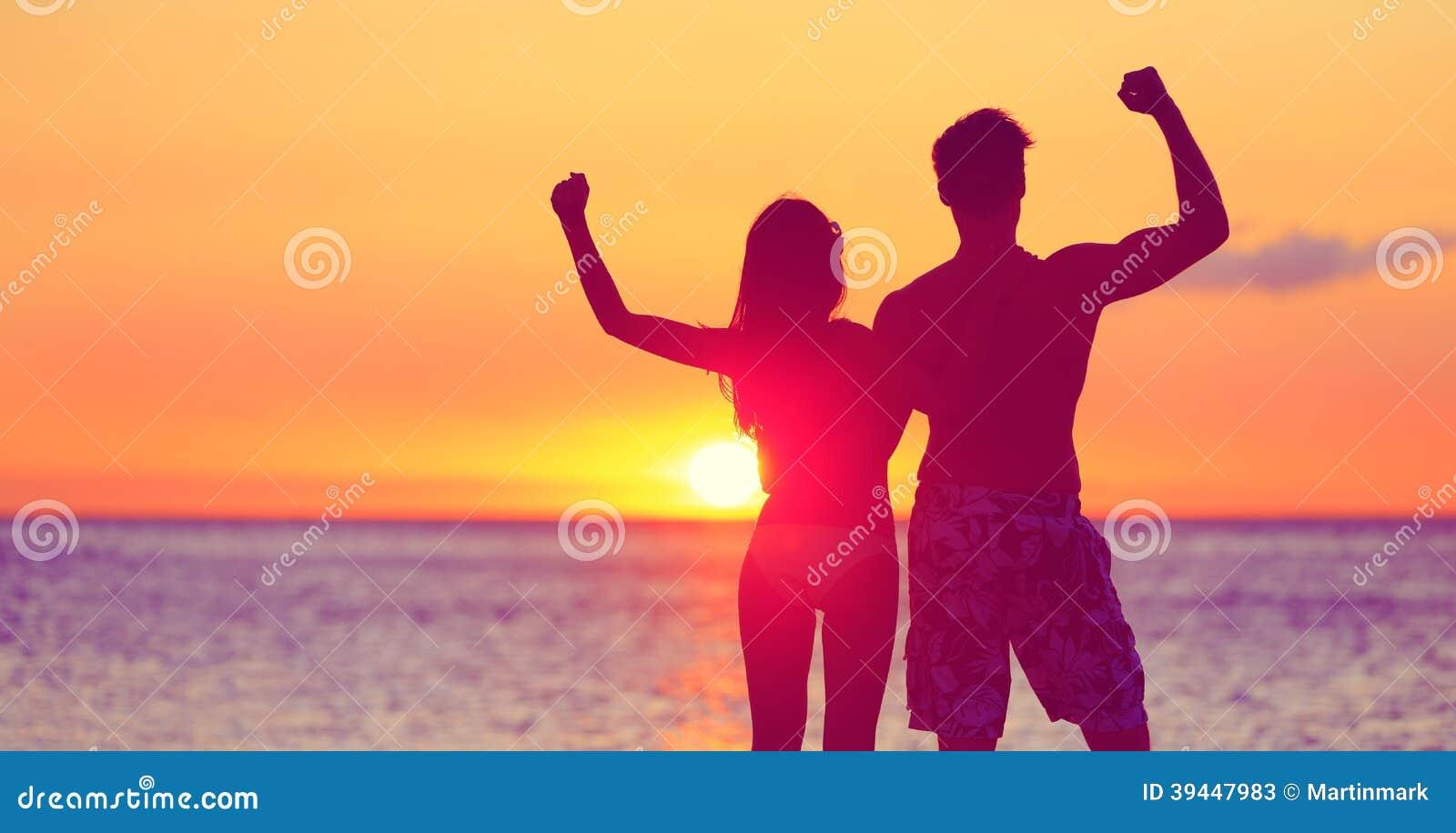Gente felice di forma fisica sulla spiaggia alla flessione di tramonto
