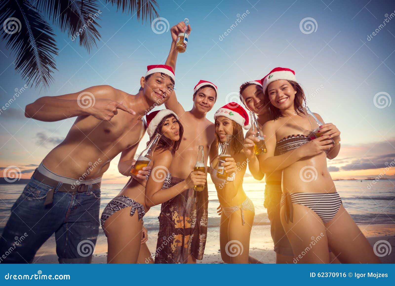 Gente feliz joven en la playa que tiene la fiesta de Navidad