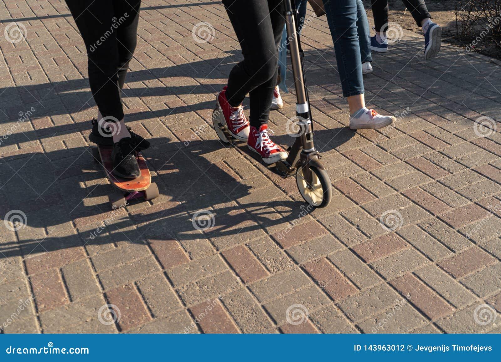Gente joven en vaqueros y zapatillas de deporte que patinan y que usan una vespa en un pavimento concreto del ladrillo