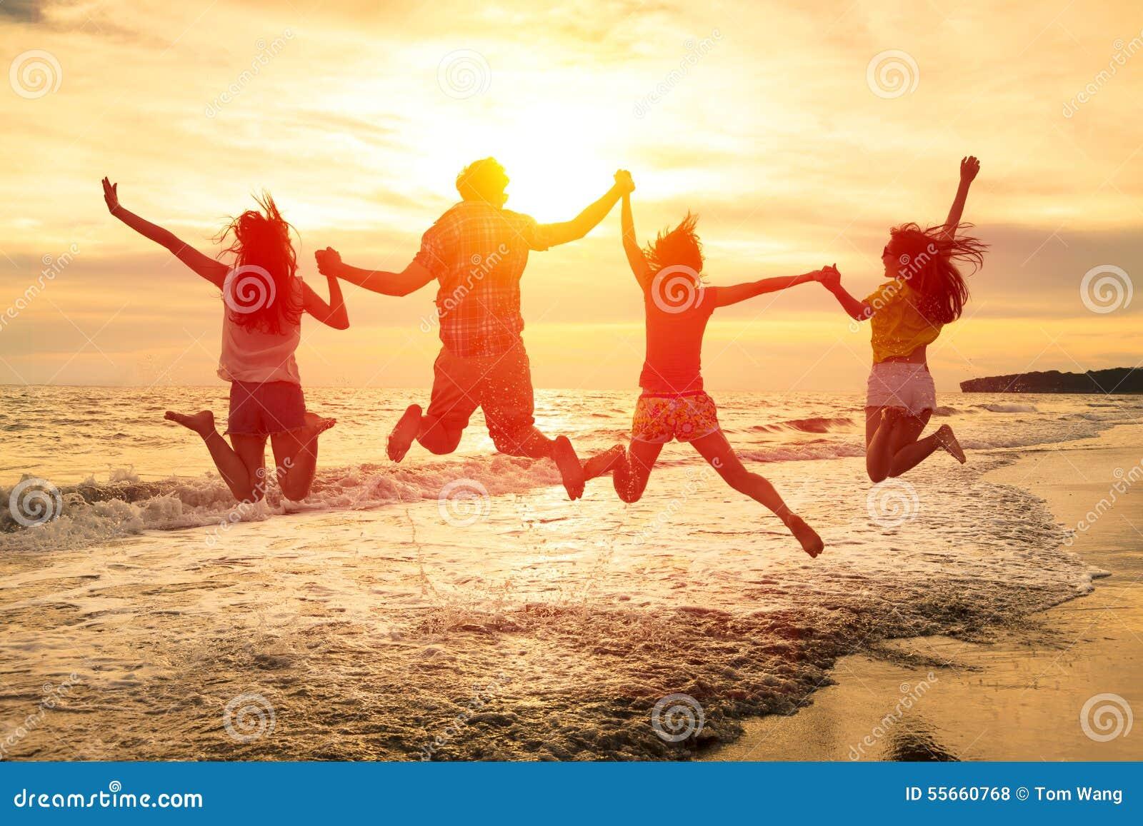 Gente joven feliz que salta en la playa