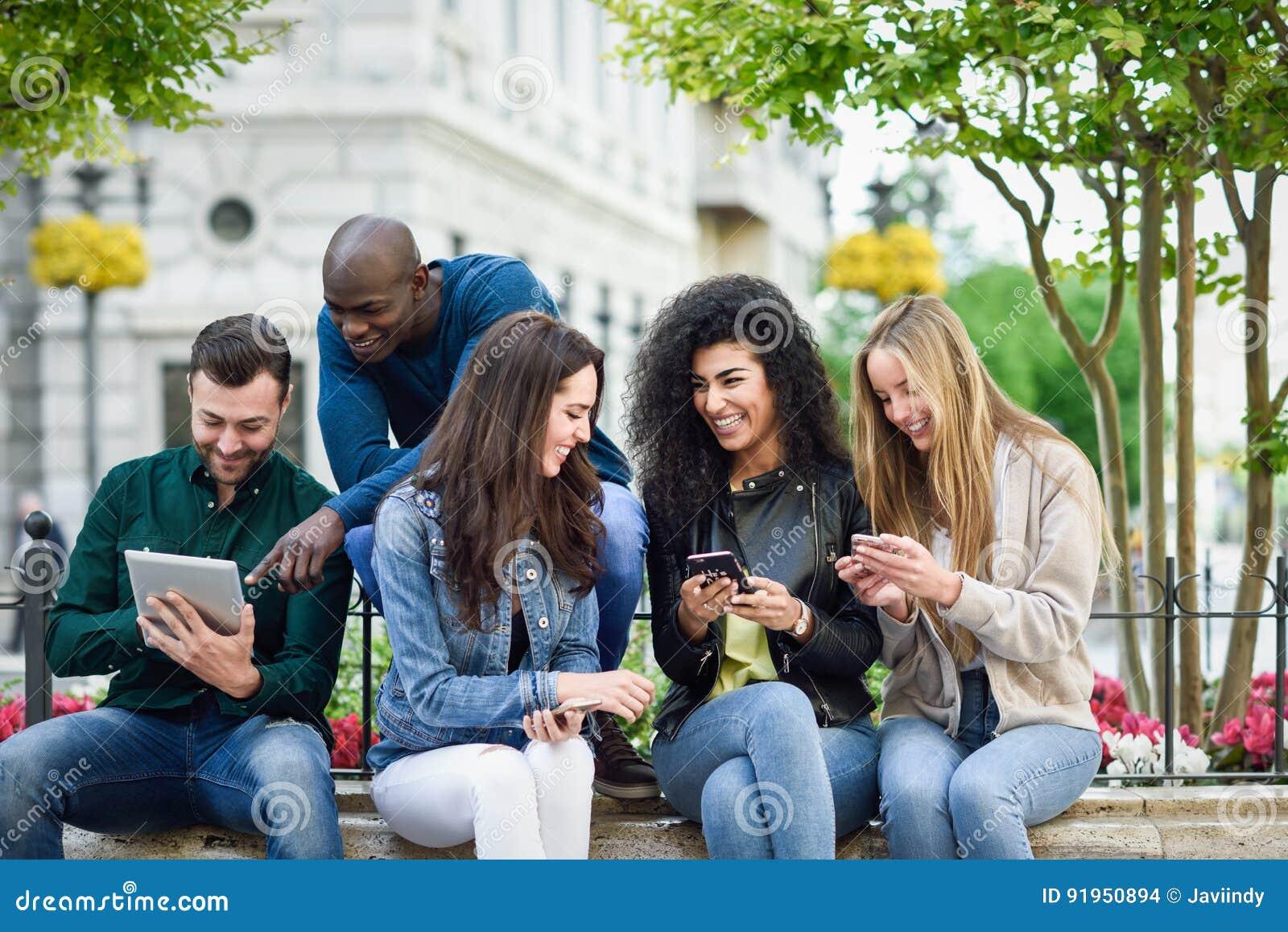 Gente joven Multi-étnica que usa smartphone y las tabletas