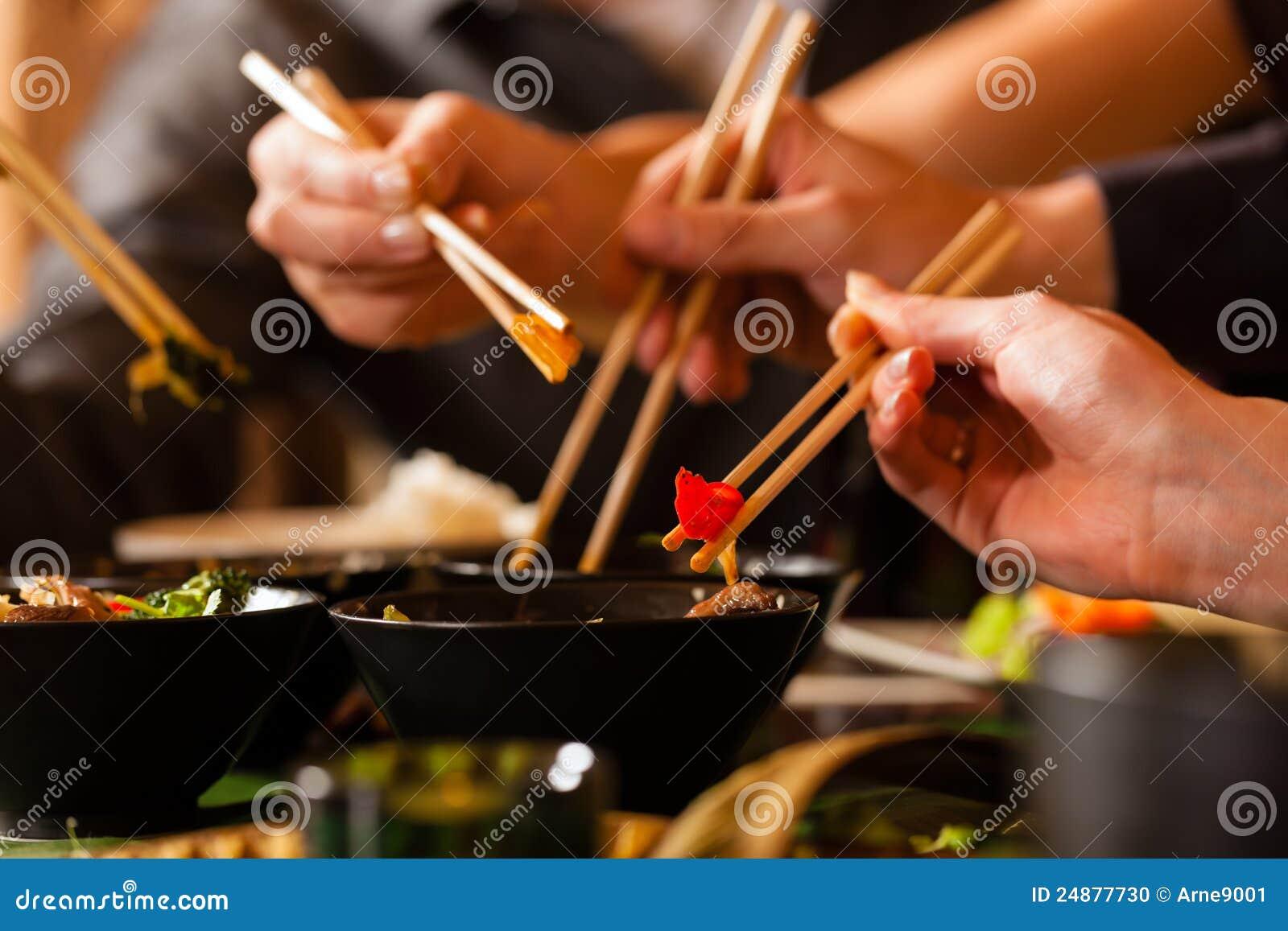 Gente joven que come en restaurante tailandés