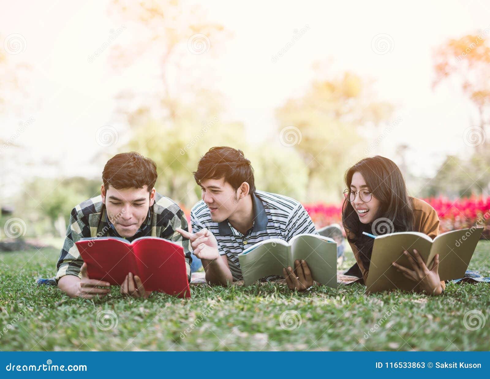 Gente joven que estudia el libro de lectura en parque estudio de la educación por leído