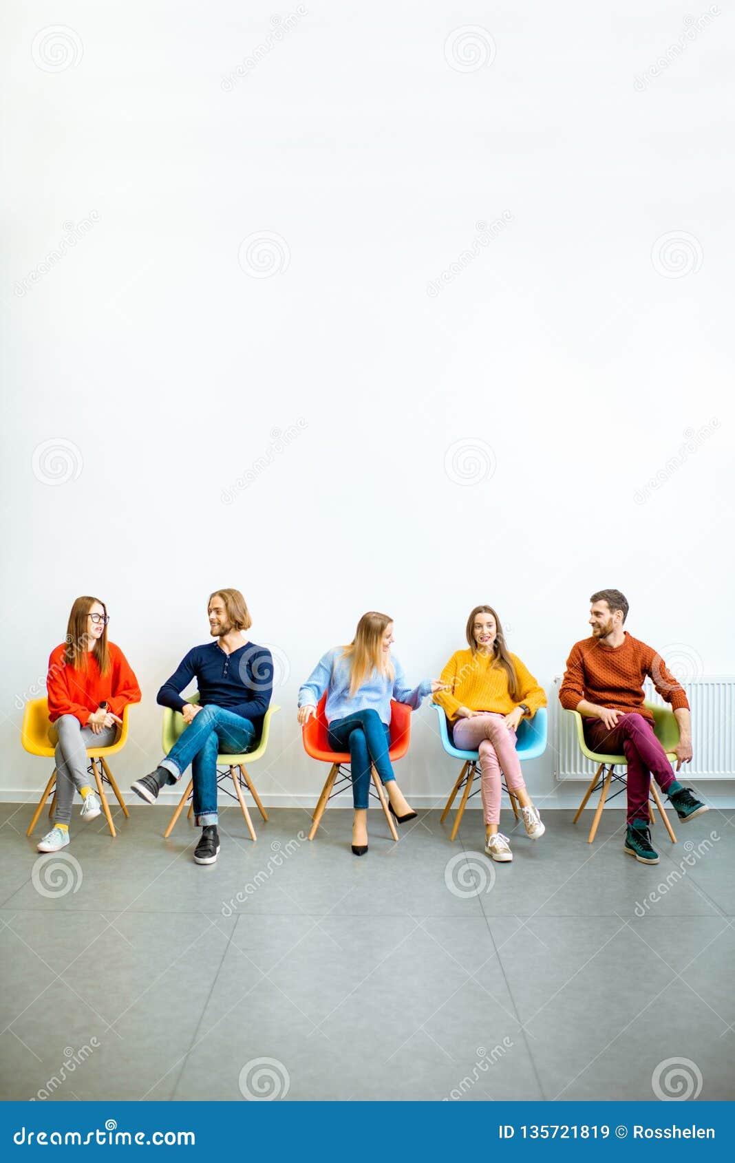 Gente joven que se sienta en fila en el fondo blanco de la pared