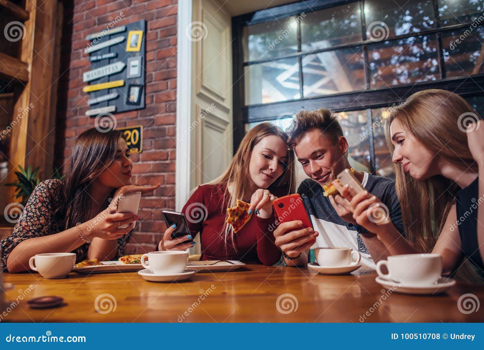 Gente joven que usa sus teléfonos móviles que se sientan alrededor de la tabla que tiene una comida en café elegante moderno
