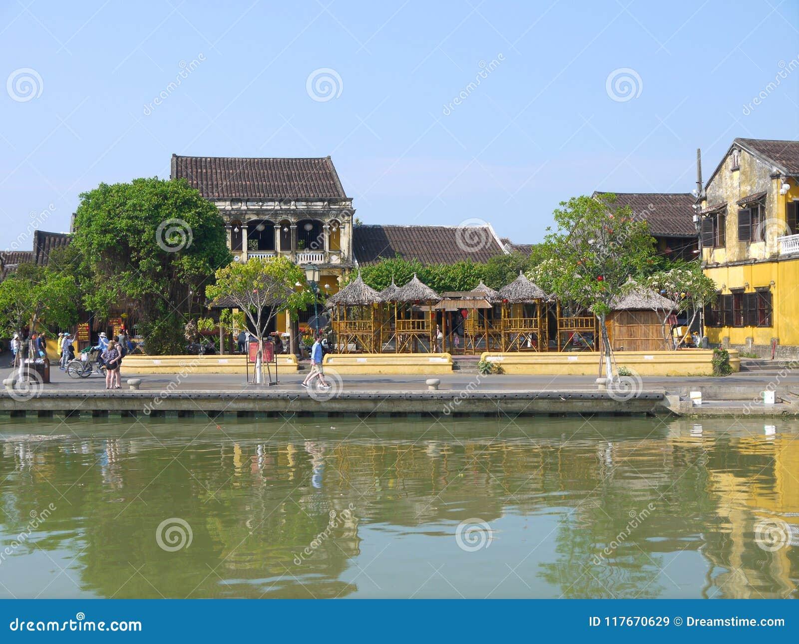 Gente locale, barche, case gialle dal fiume e turisti nella città antica di Hoi An