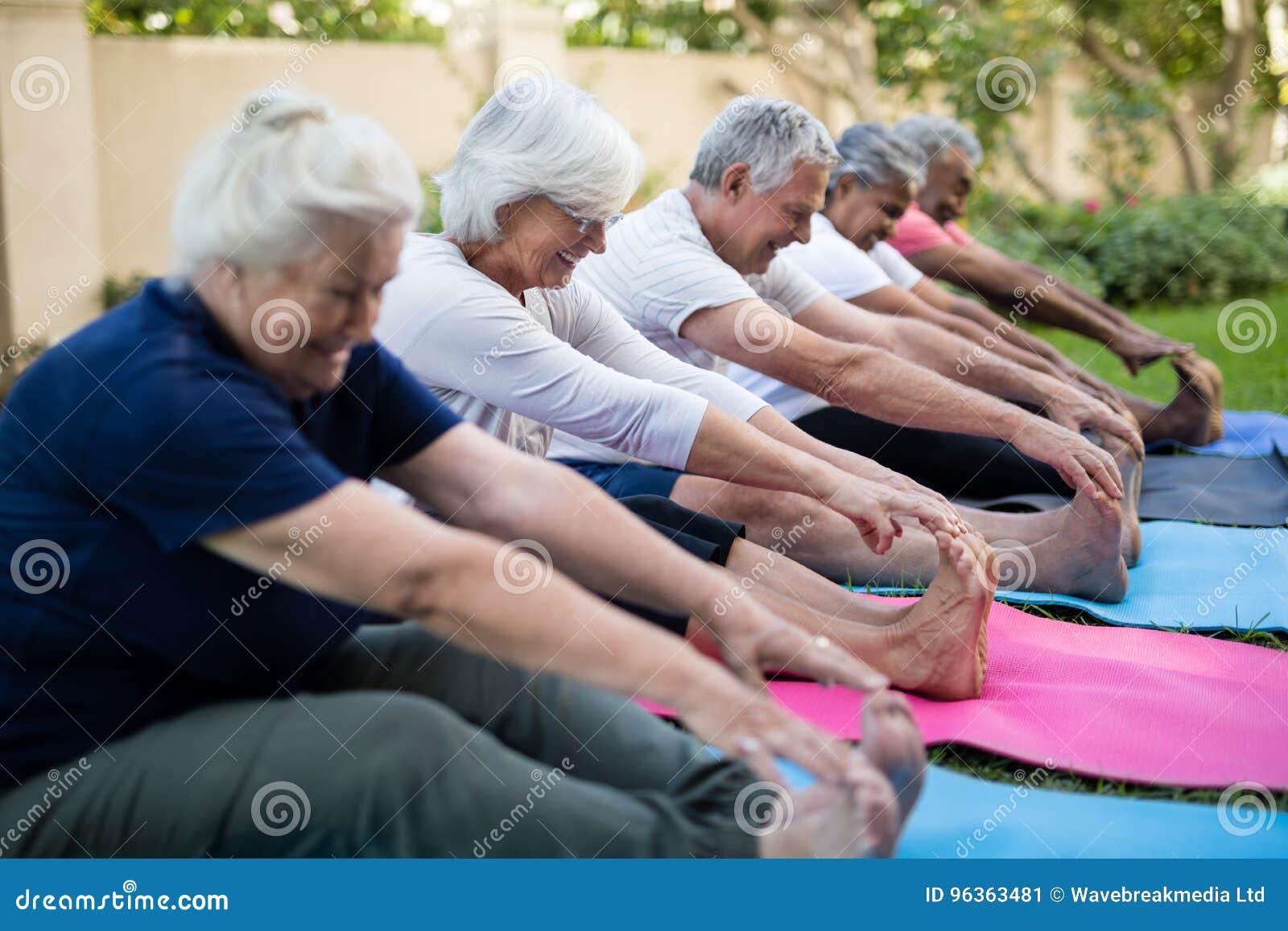 Gente mayor multi-étnica sonriente que hace estirando ejercicio
