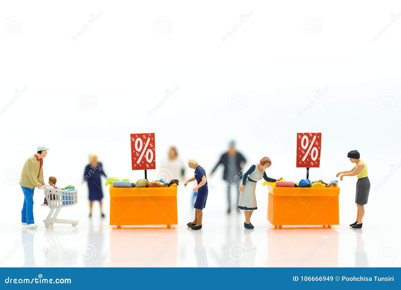 Gente miniatura: Compradores con el descuento para los artículos que hacen compras usando como concepto del negocio de las compra