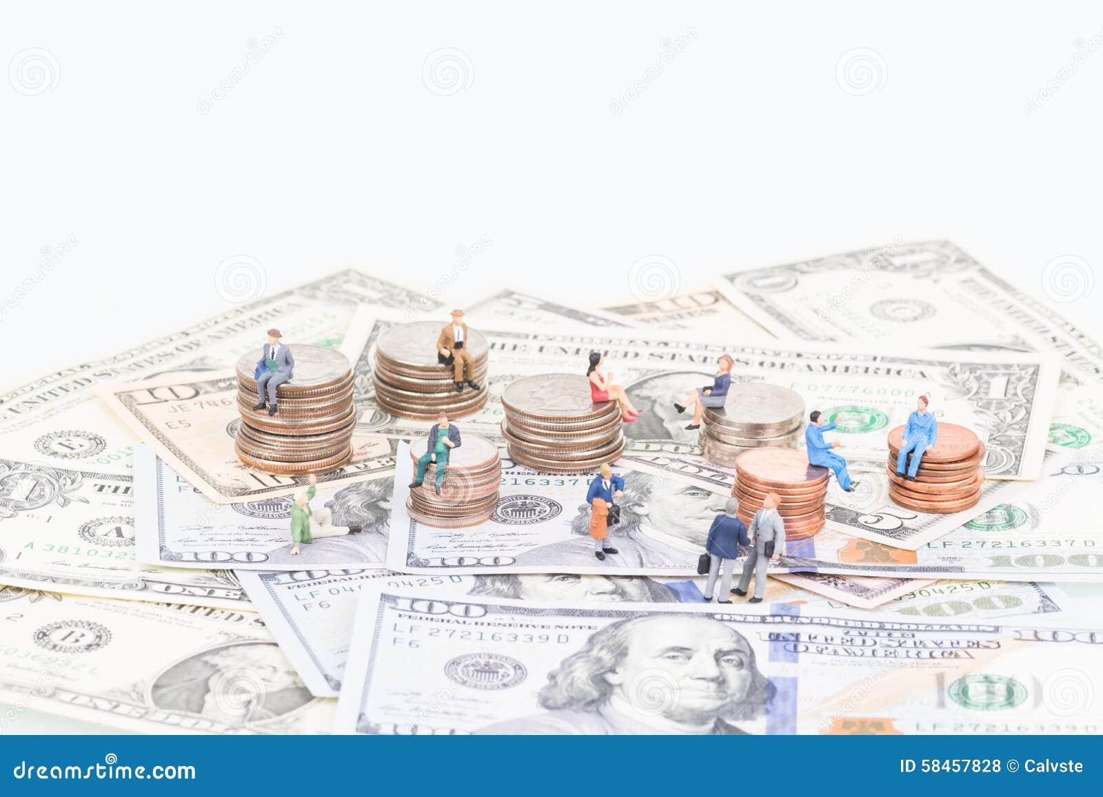 Gente miniatura en las monedas y los billetes de banco
