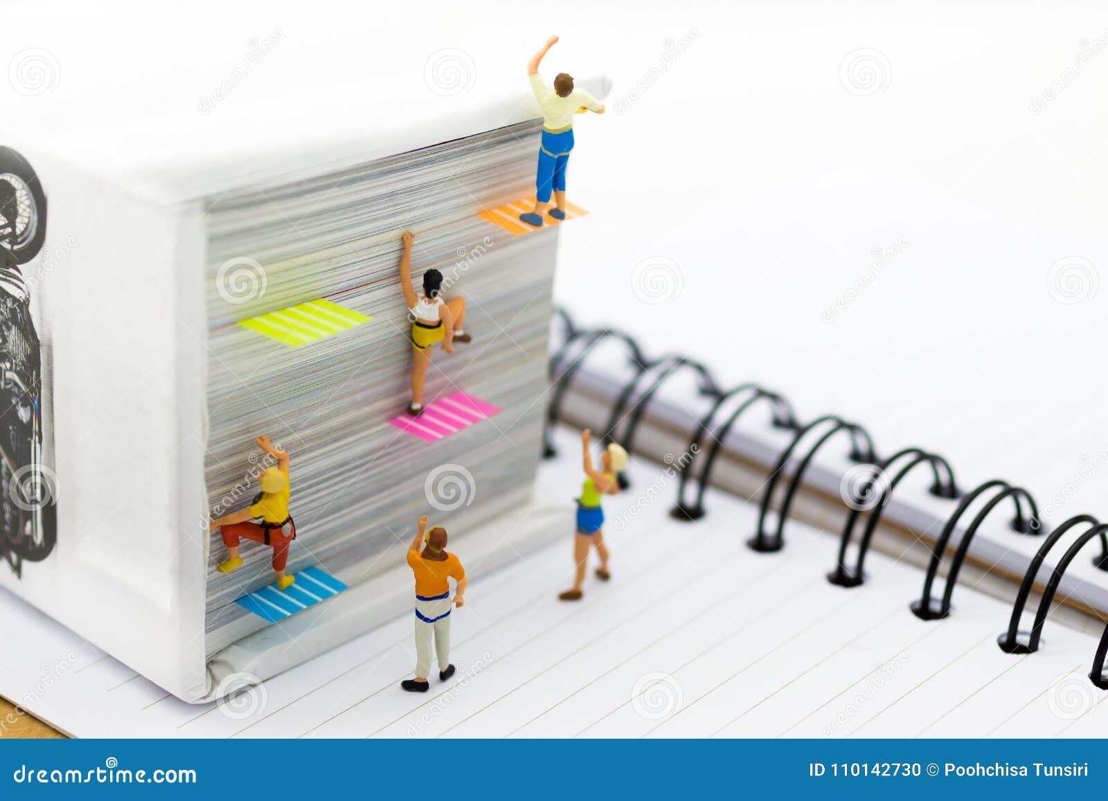 Gente miniatura: Escalador que sube en el libro Uso de la imagen para aprender, concepto de la educación