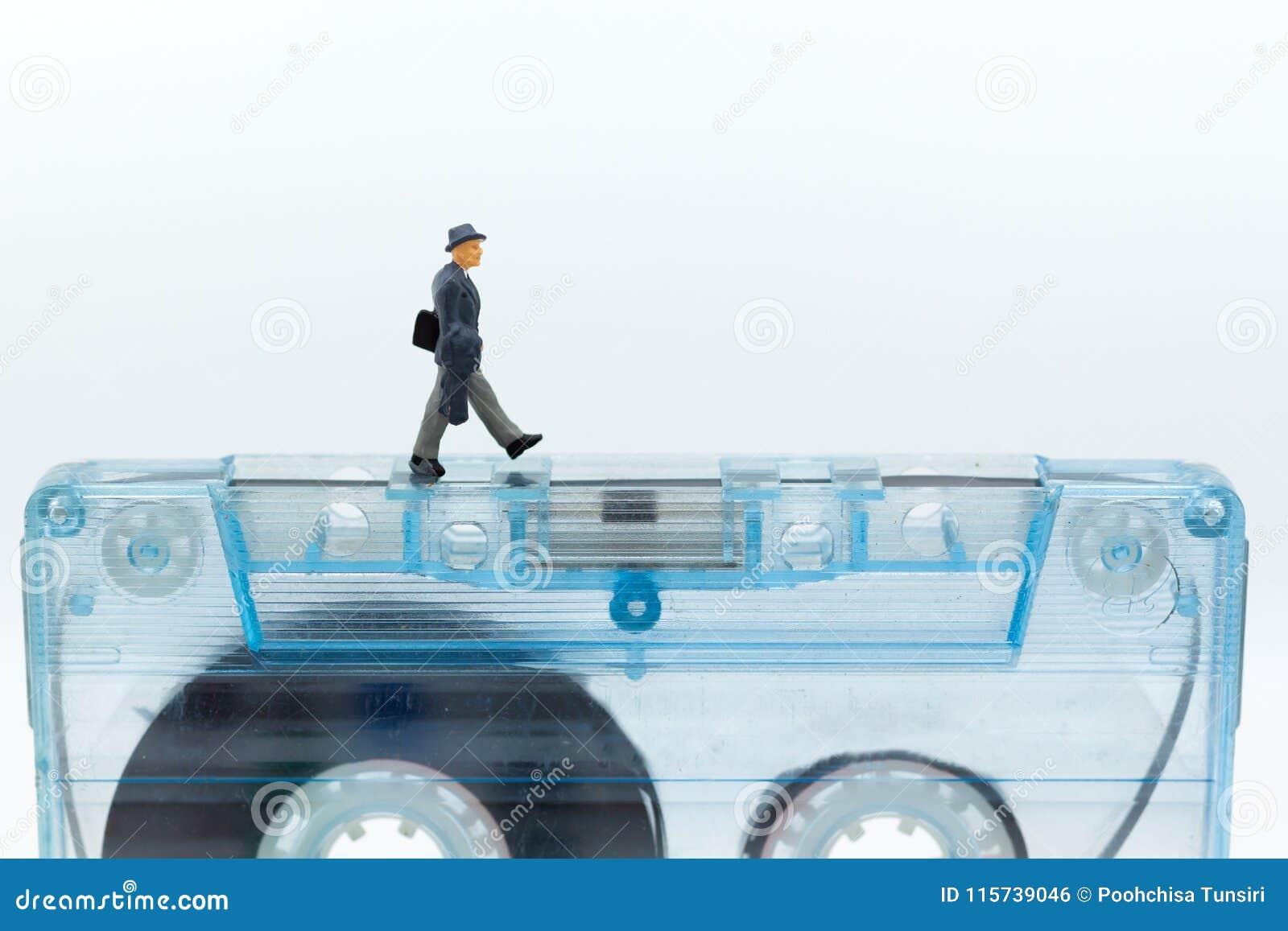 Gente miniatura: Uomo d affari che cammina sulla cassetta compatta immagine