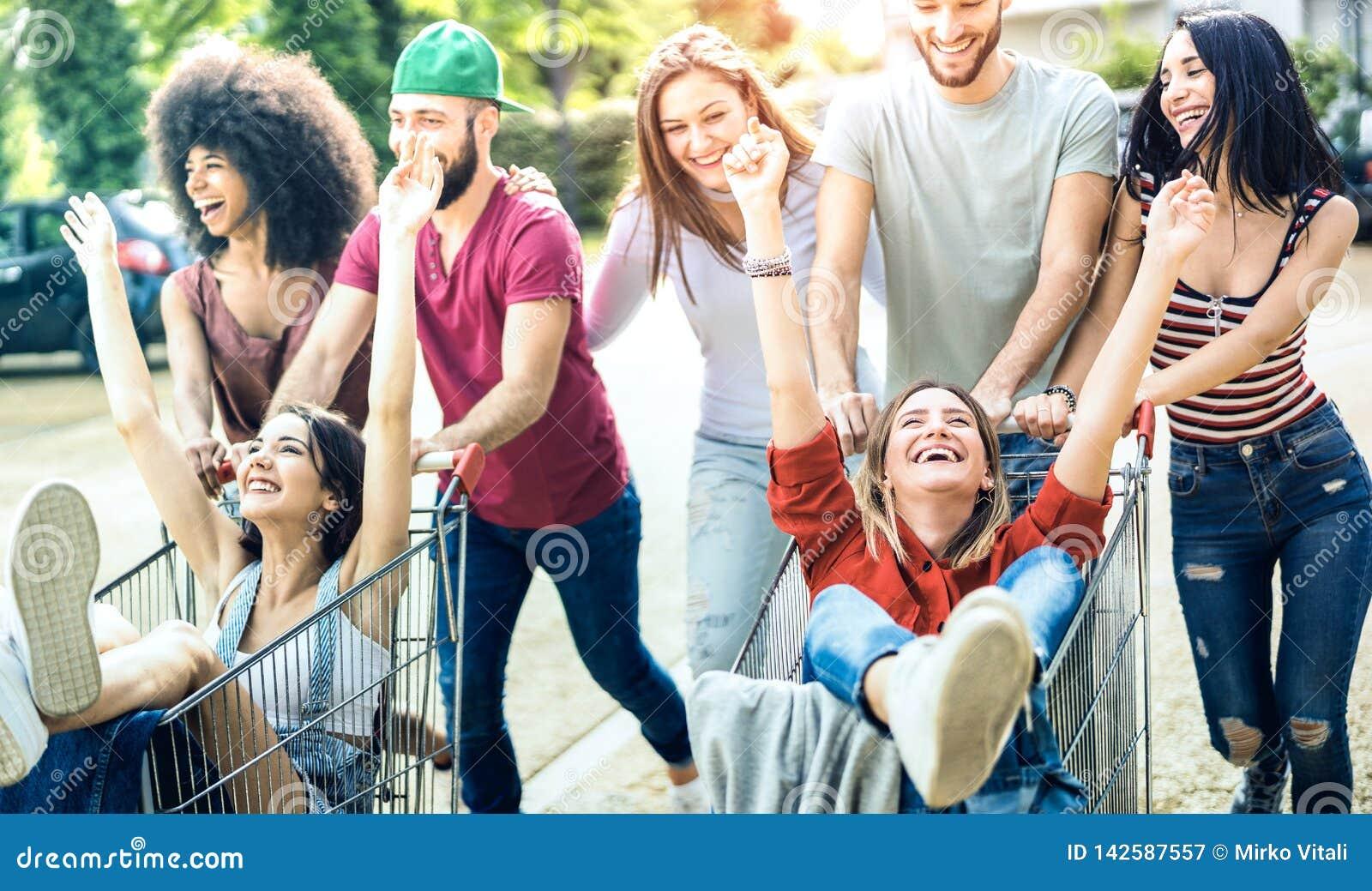 Gente multirracial joven que se divierte así como el carro de la compra - amigos de Millenial que comparten tiempo con las carret