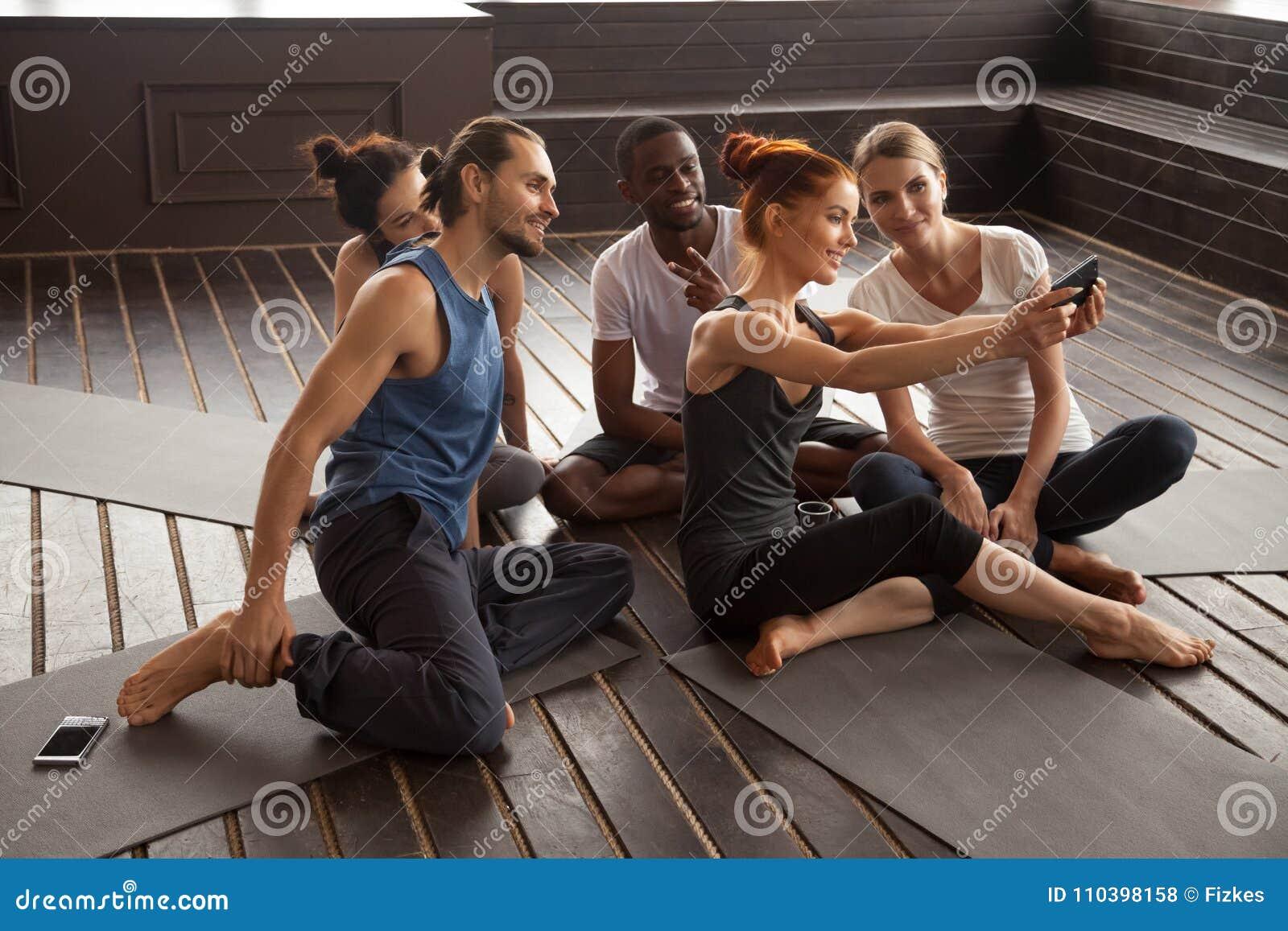 Gente multirracial sonriente que hace el selfie en smartphone en la yoga t