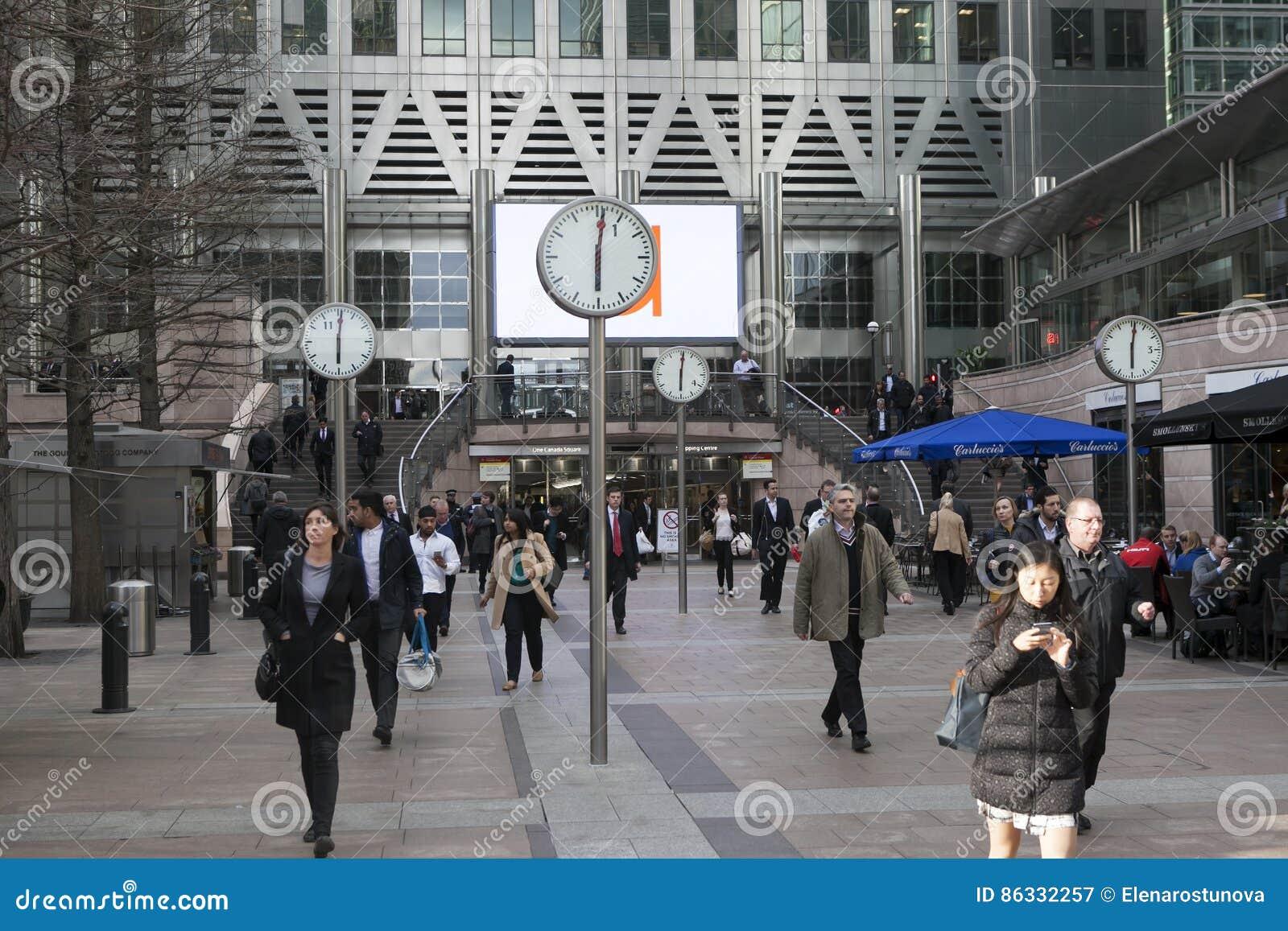Gente non identificata alla passeggiata di Canary Wharf fra gli orologi Sei orologi pubblici da Konstantin Grcic sono stati proge