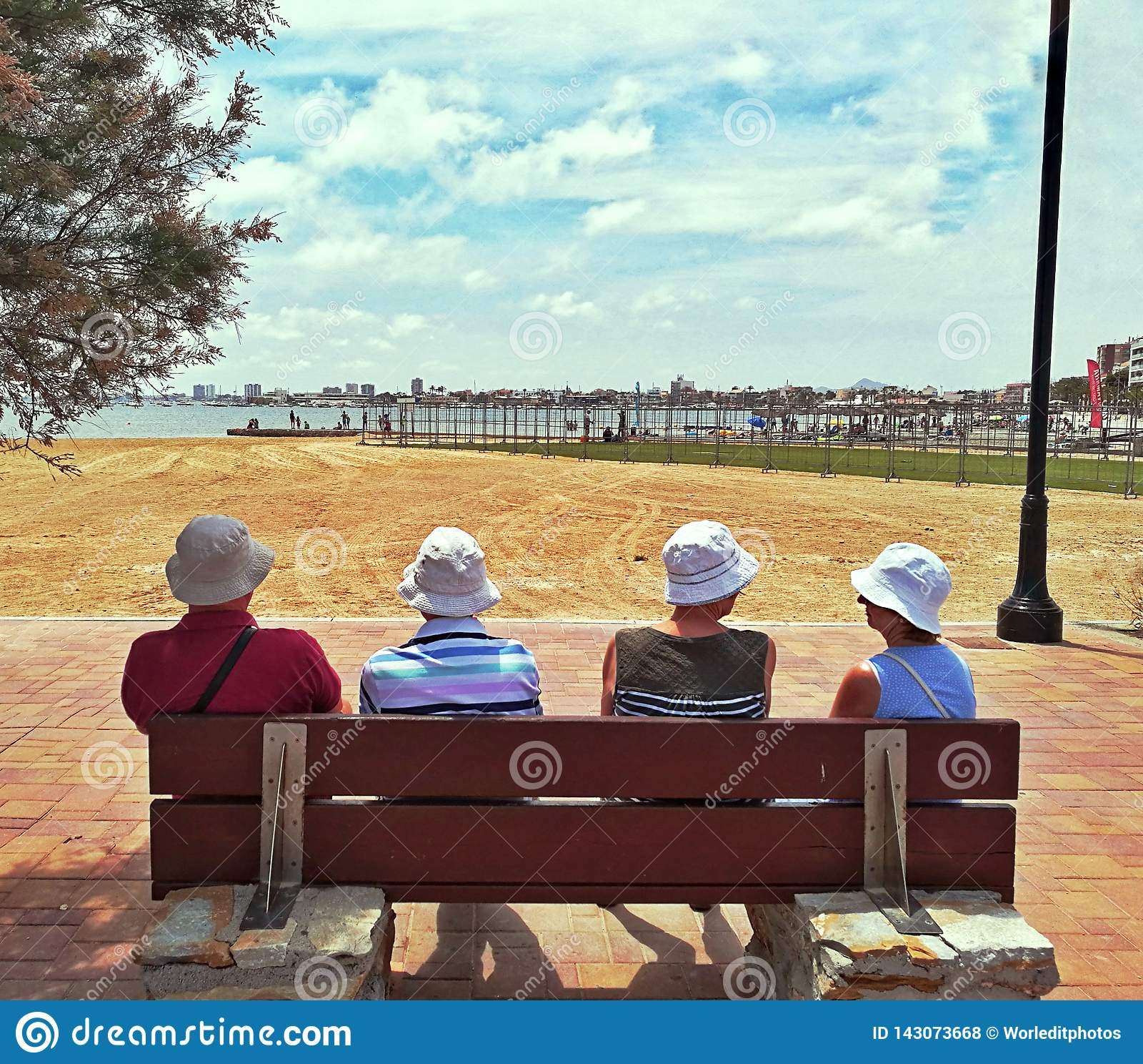 Gente più anziana che affronta il mare per sedersi sul banco