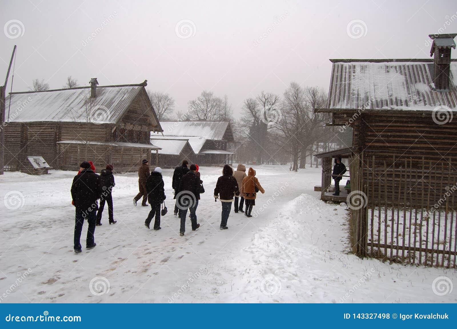 Gente que camina cerca de casa de madera en el invierno
