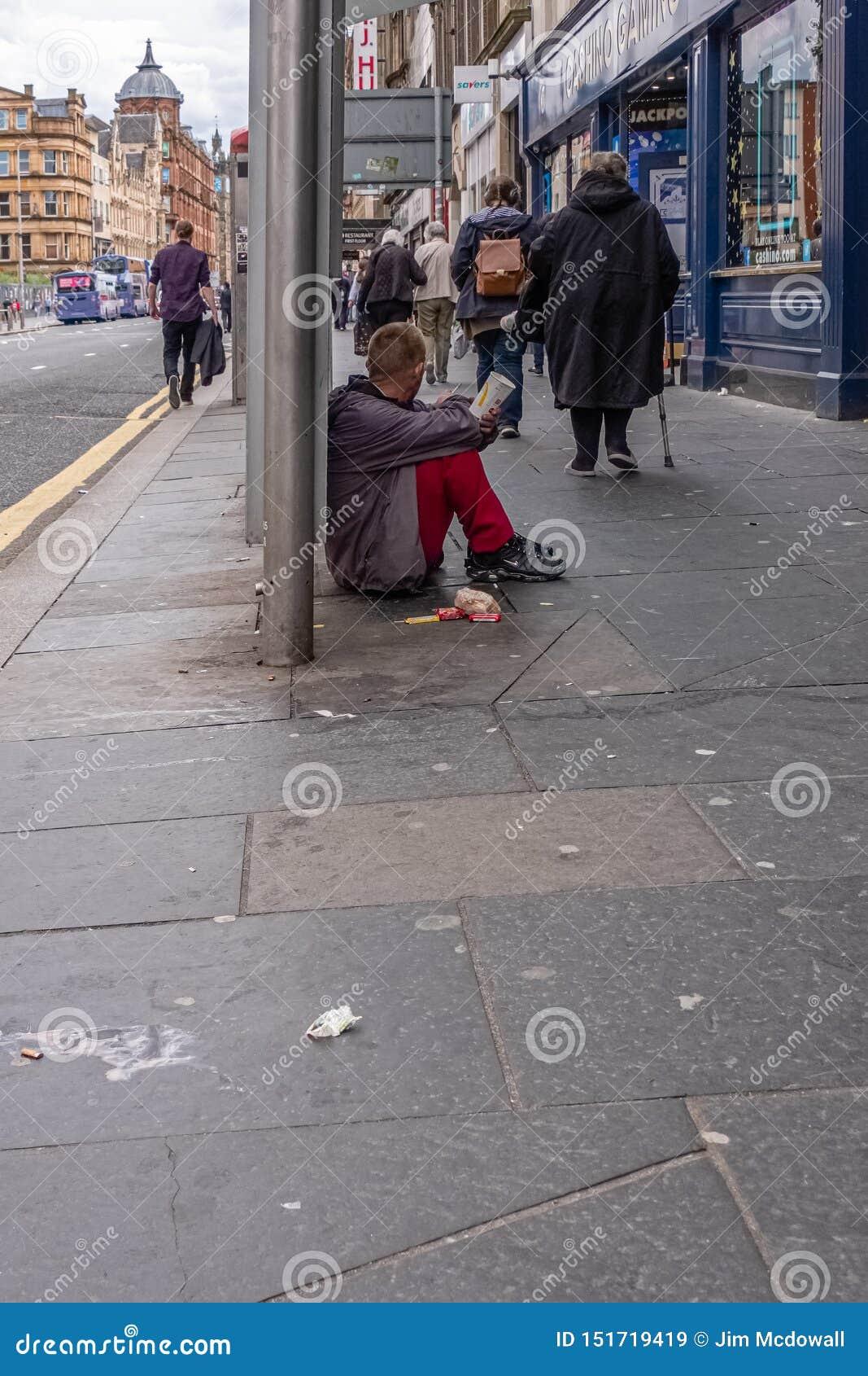 Gente que camina más allá de un caballero masculino que localiza en el pavimento sucio con una taza de papel de mcdonald que apel