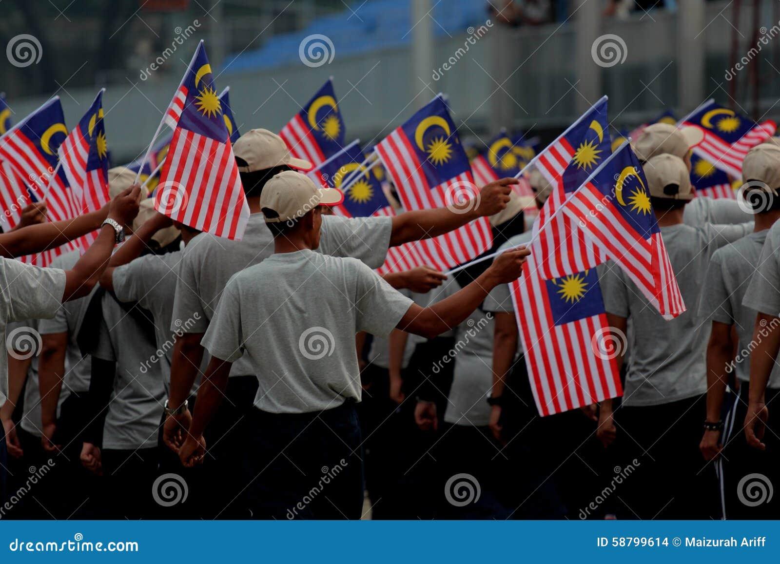 Gente que desfila las banderas del malasio en la conjunción del Día de la Independencia de Malasia