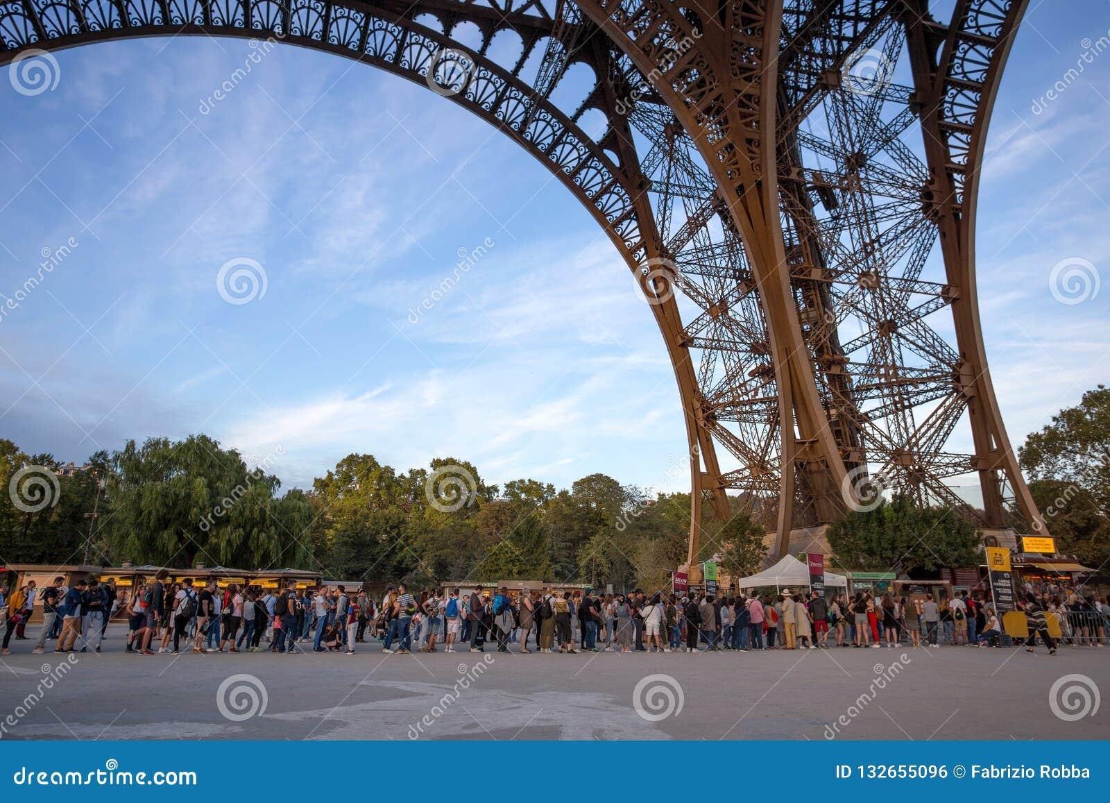 Gente que espera en cola larga en la torre Eiffel en París, Francia
