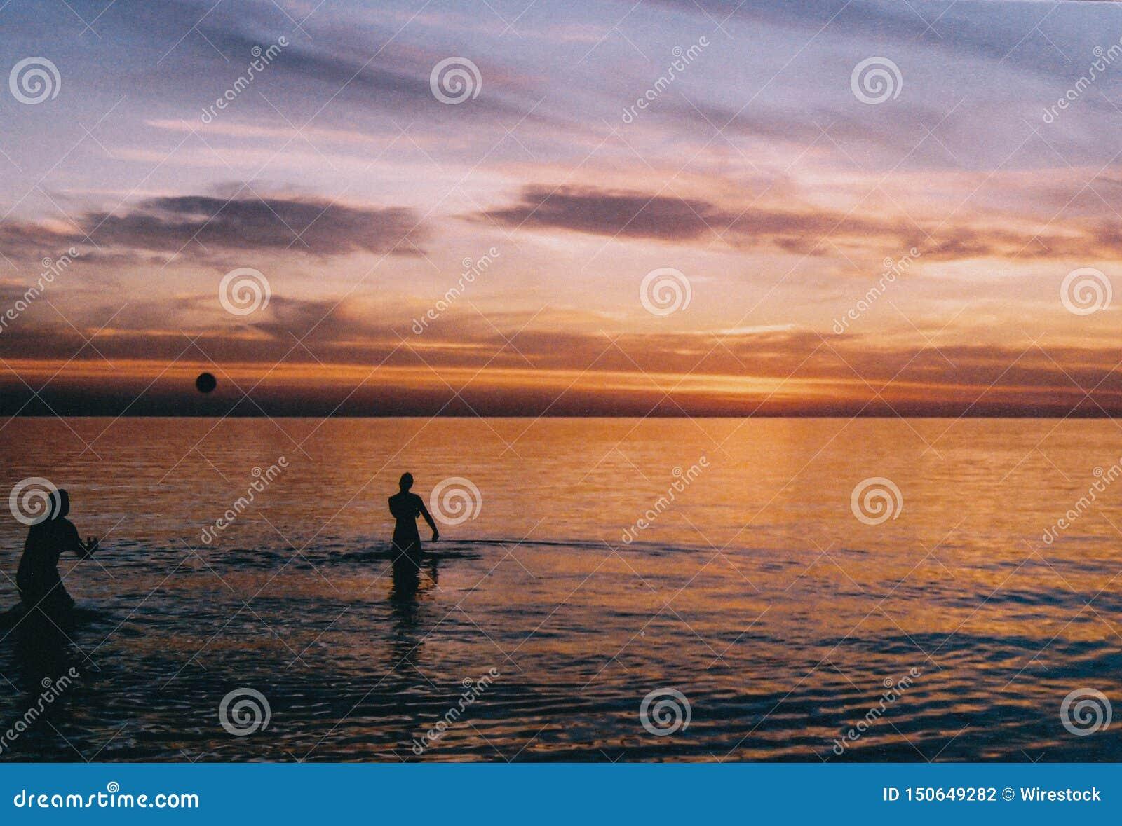 Gente que juega con una bola en la playa en el agua