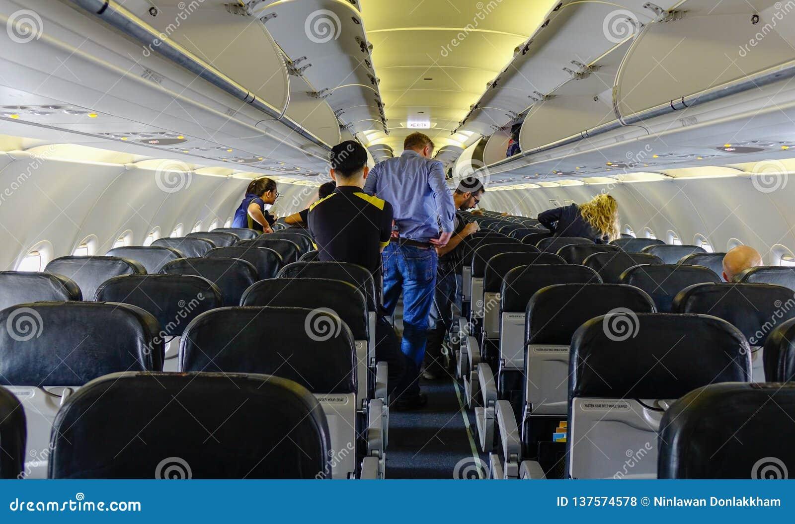 Gente que se coloca y que se sienta en un aeroplano