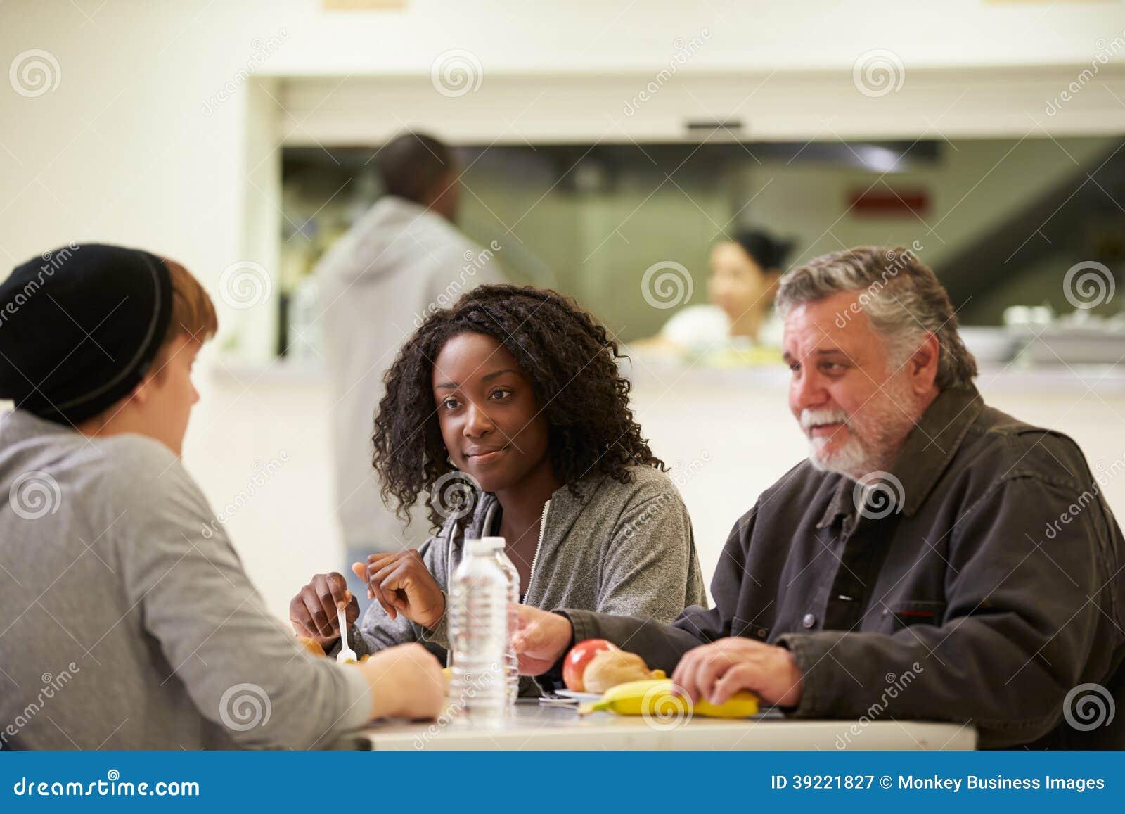 Gente que se sienta en la tabla que come la comida en refugio para personas sin techo