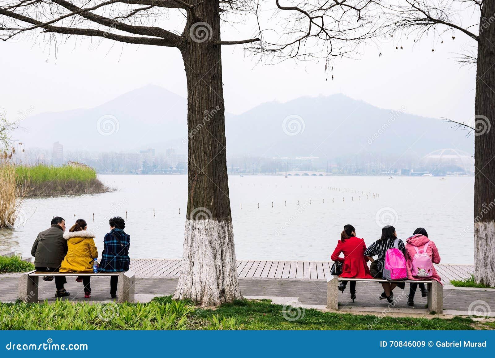 Gente que se sienta por el lago Xuanwu