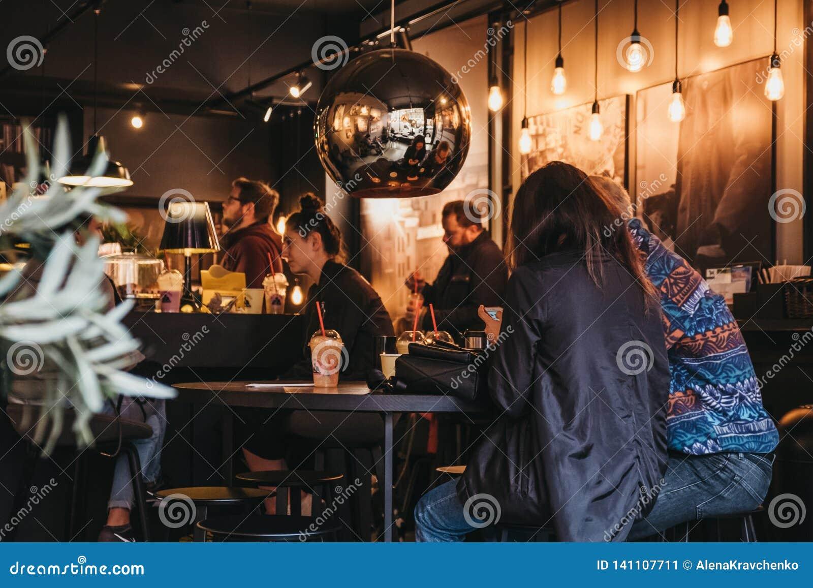 Gente que tiene bebidas dentro de Joe y del café del jugo en Hampstead, Londres, Reino Unido