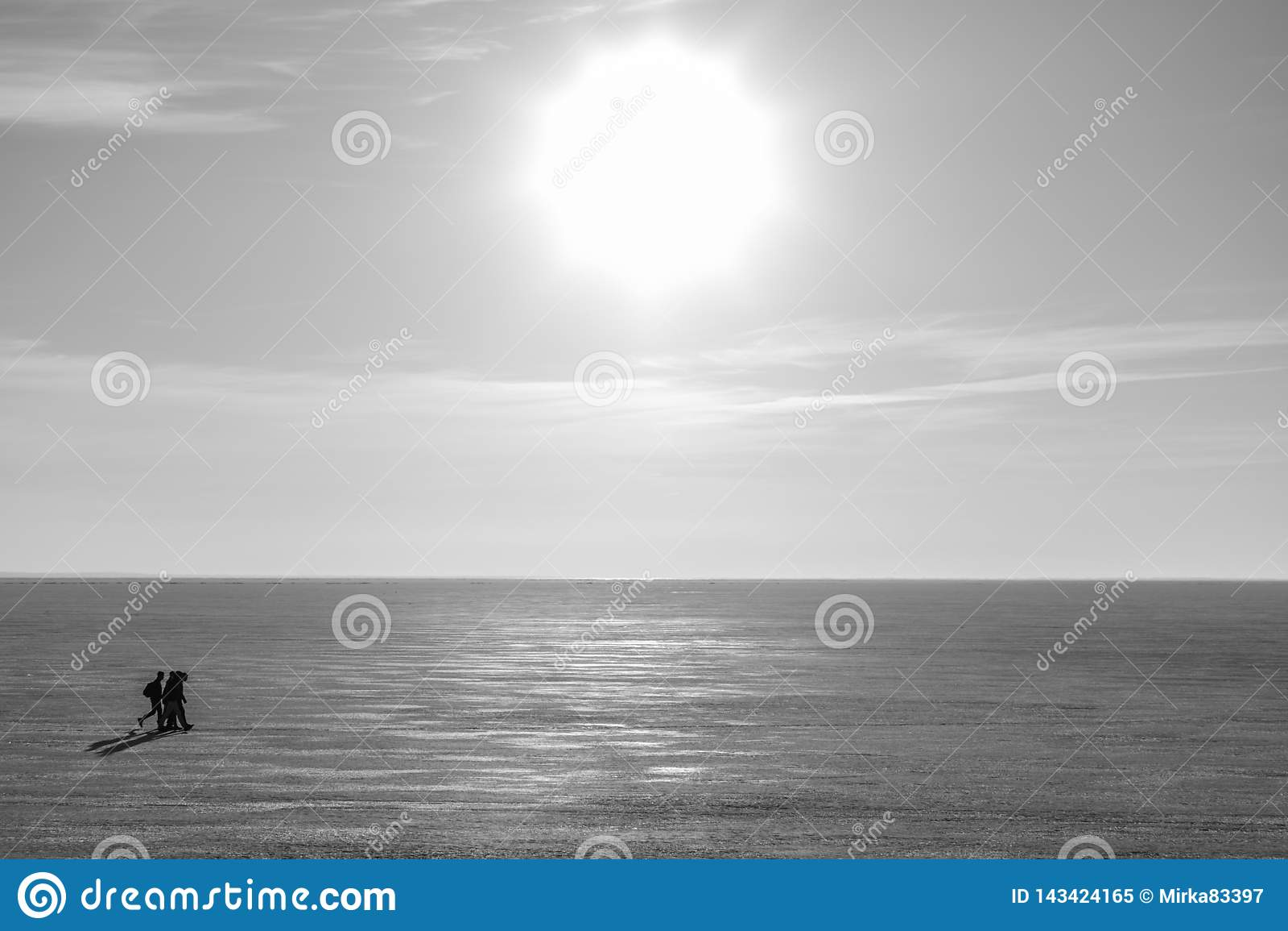 Gente que viene en el hielo a través del río o del lago en el día soleado del invierno
